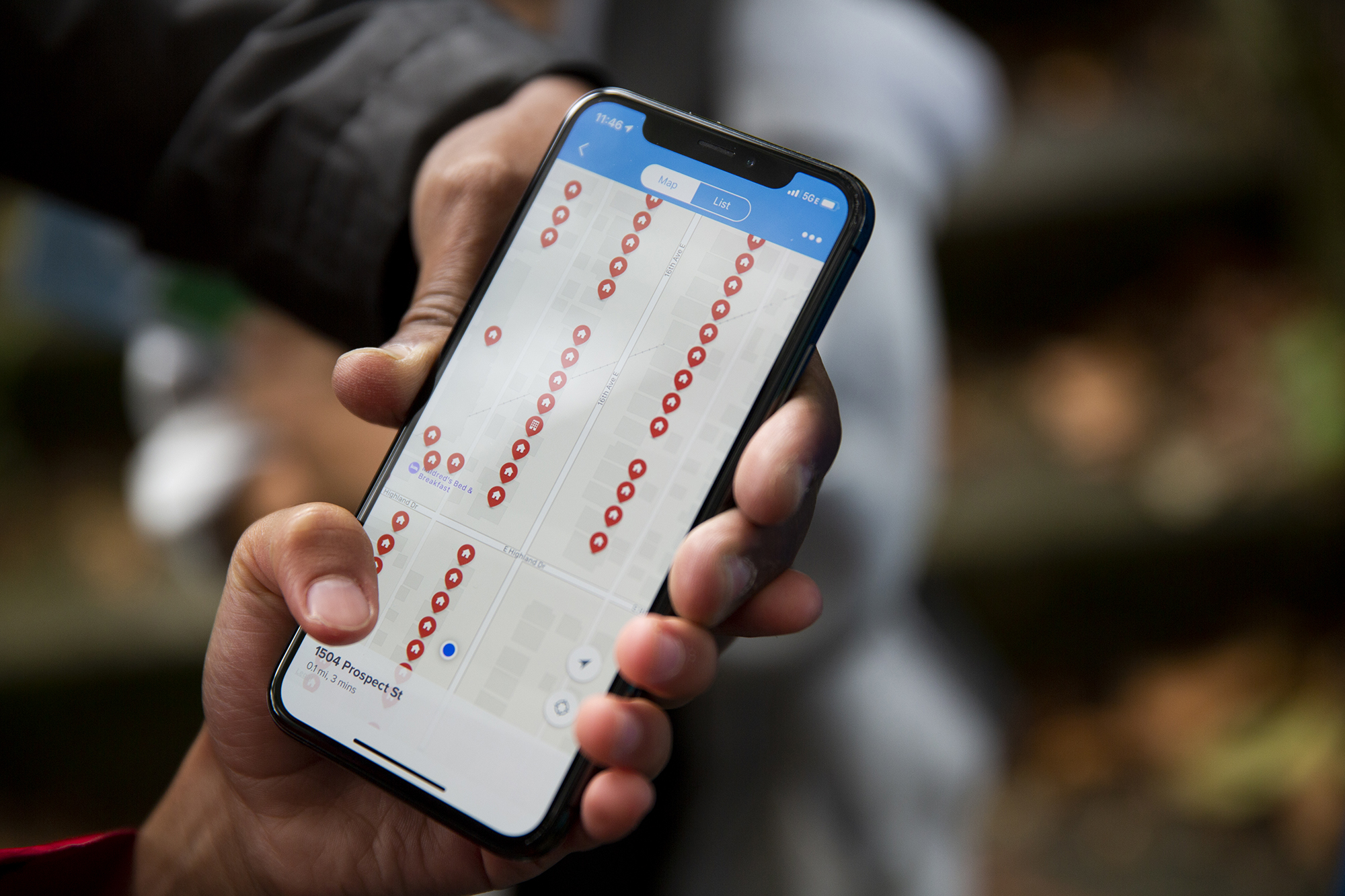 A volunteer holds a smart phone showing a map of households visited by the campaign.