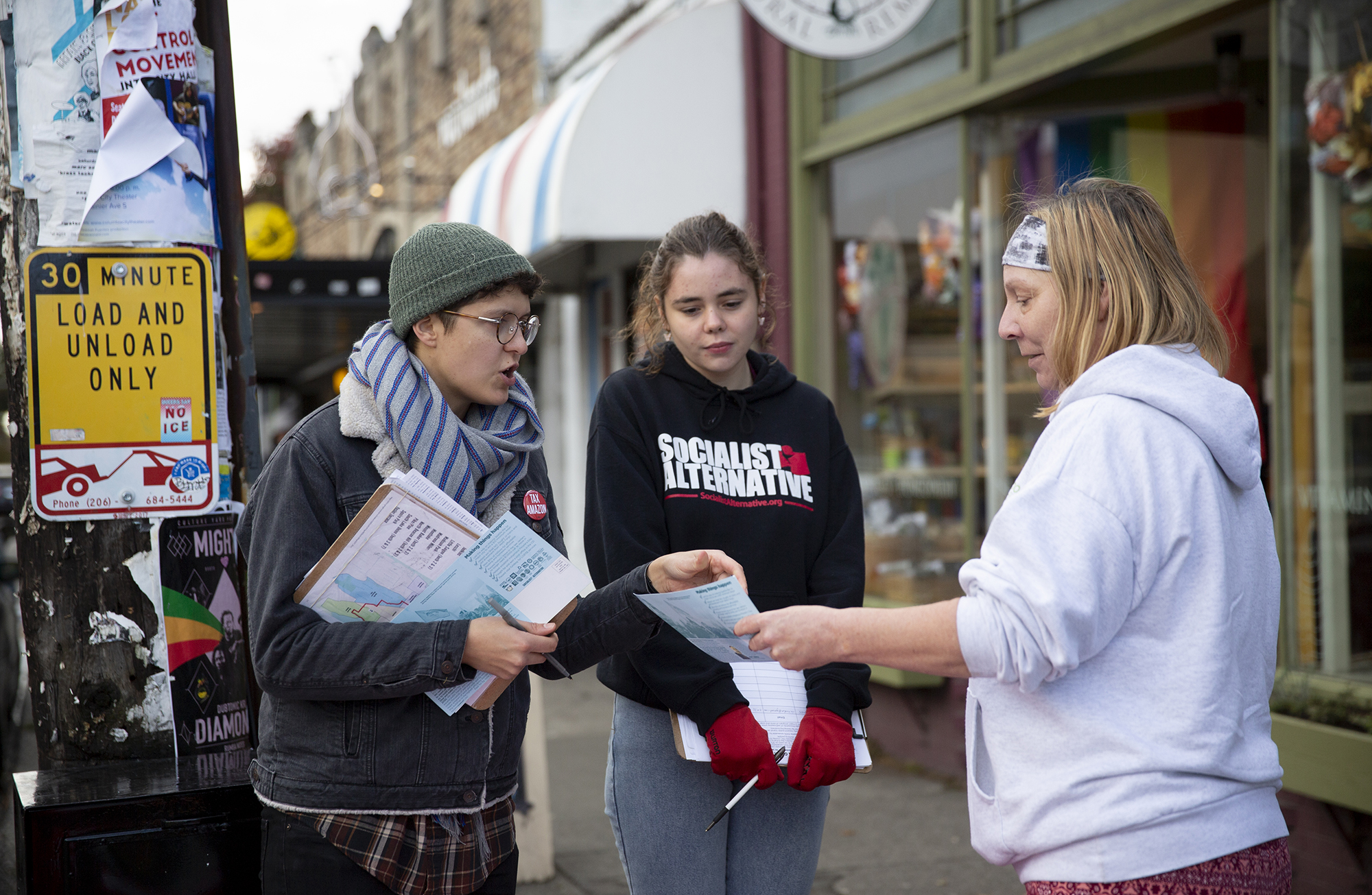Two volunteers with the Sawant campaign talk to a person on the sidewalk.