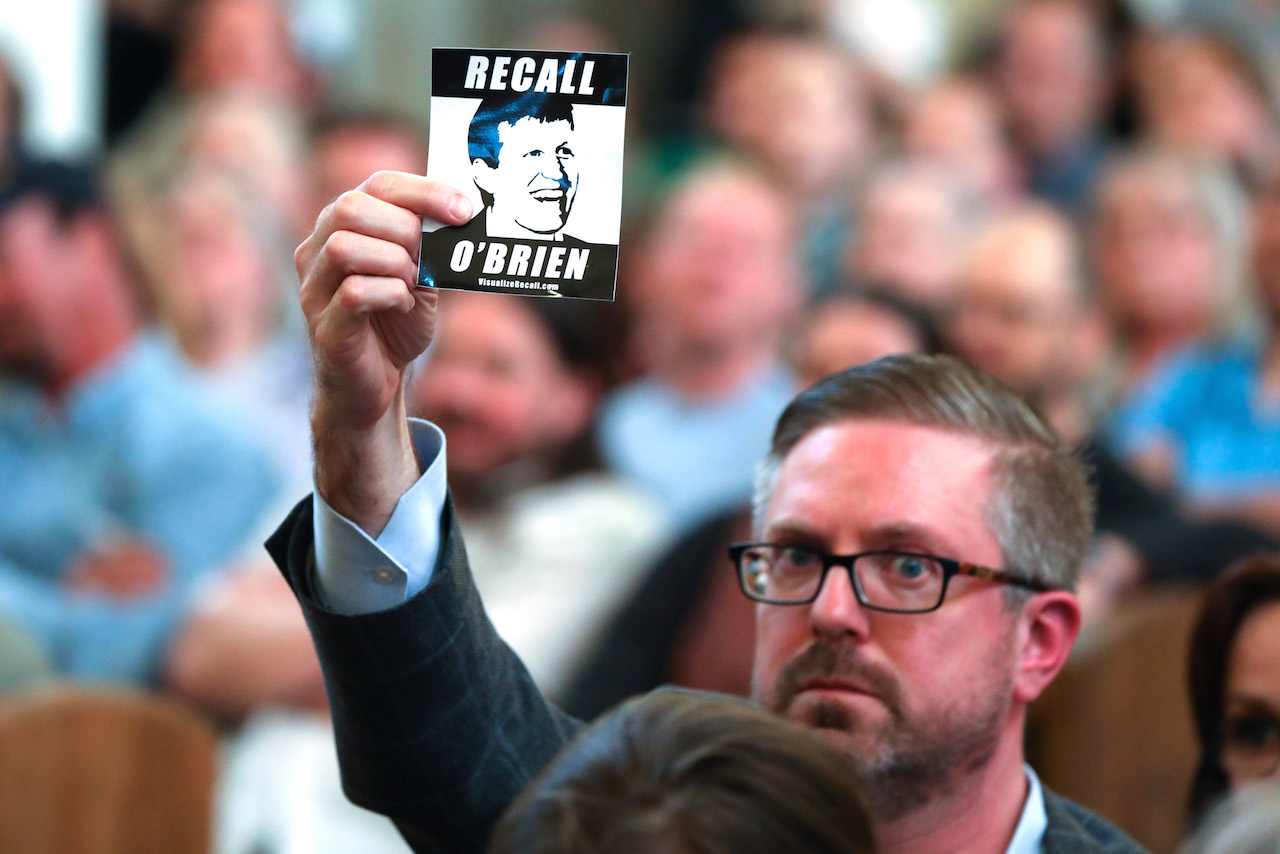 Man holds recall mike o'brien sticker