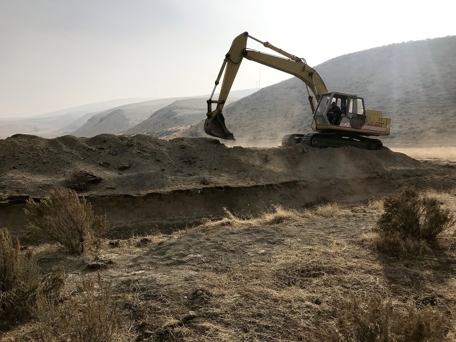 A backhoe digs near a fault scarp