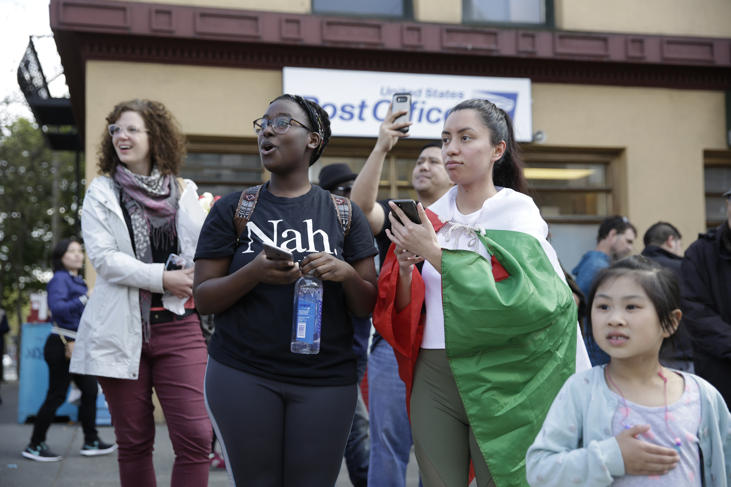 Zaria Smiley (L), 21, and Darlene Hadley, 21, both of Seattle, stop to watch before joining in the march in the International District at the annual May Day March for Workers and Immigrant Rights in Seattle, May 1, 2018. (Jason Redmond for Crosscut)
