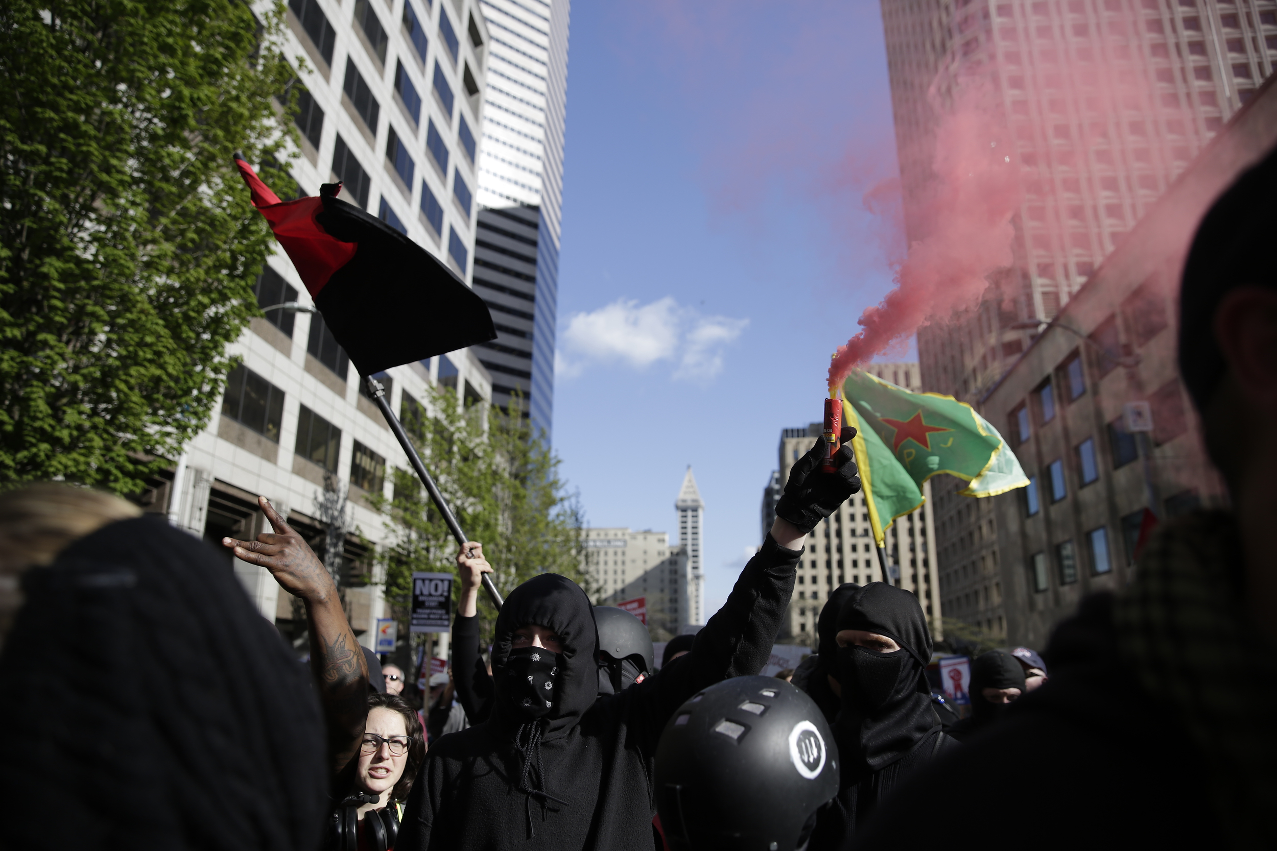 Individuals dressed in black, who wished to remain anonymous, carry a smoke flare and march in the annual May Day March for Workers and Immigrant Rights in Seattle, May 1, 2018.