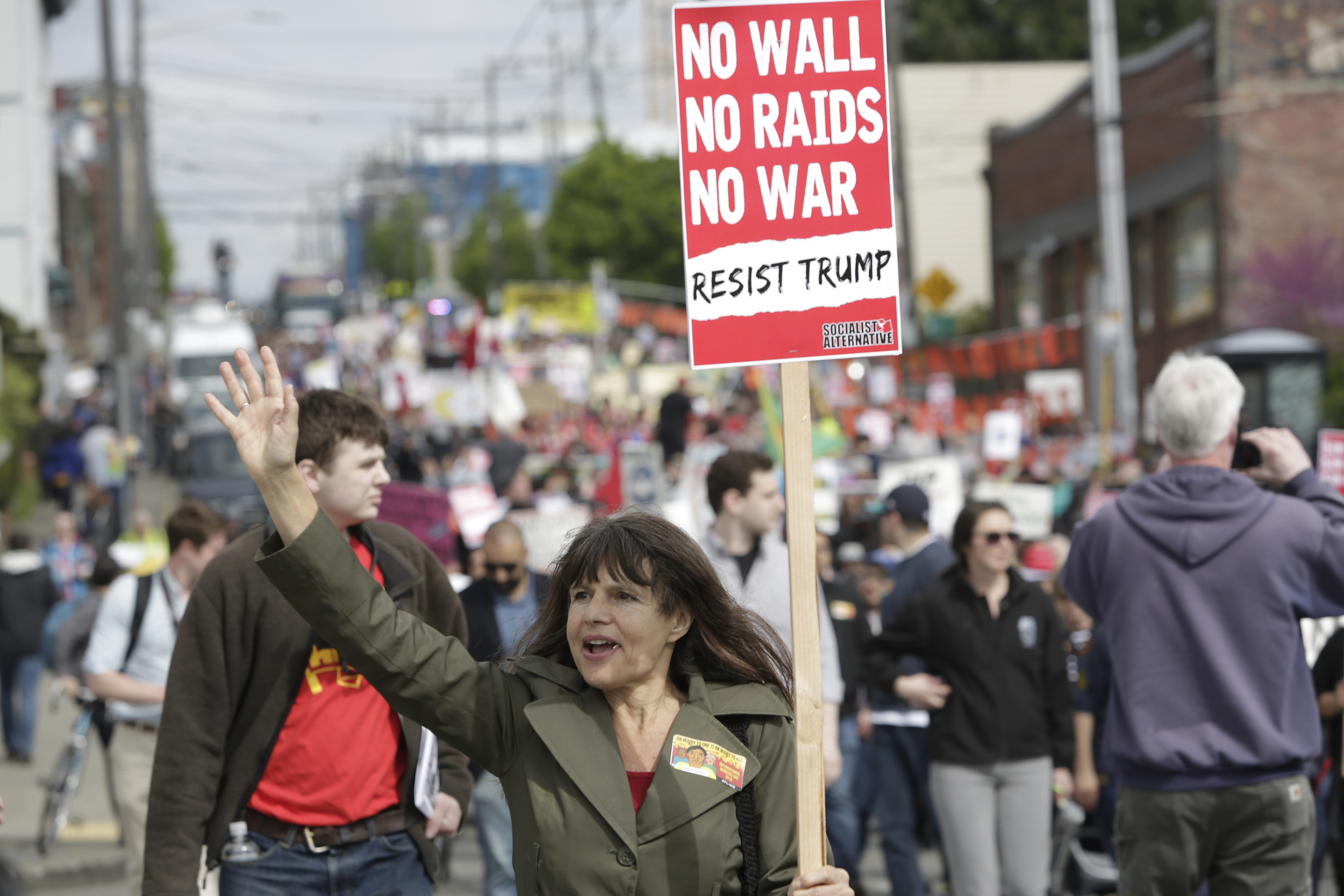 Preschool teacher Lauren Tozzi of Seattle, who says she never misses a march, waves to onlookers during the annual May Day March for Workers and Immigrant Rights in Seattle, May 1, 2018. (Jason Redmond for Crosscut)