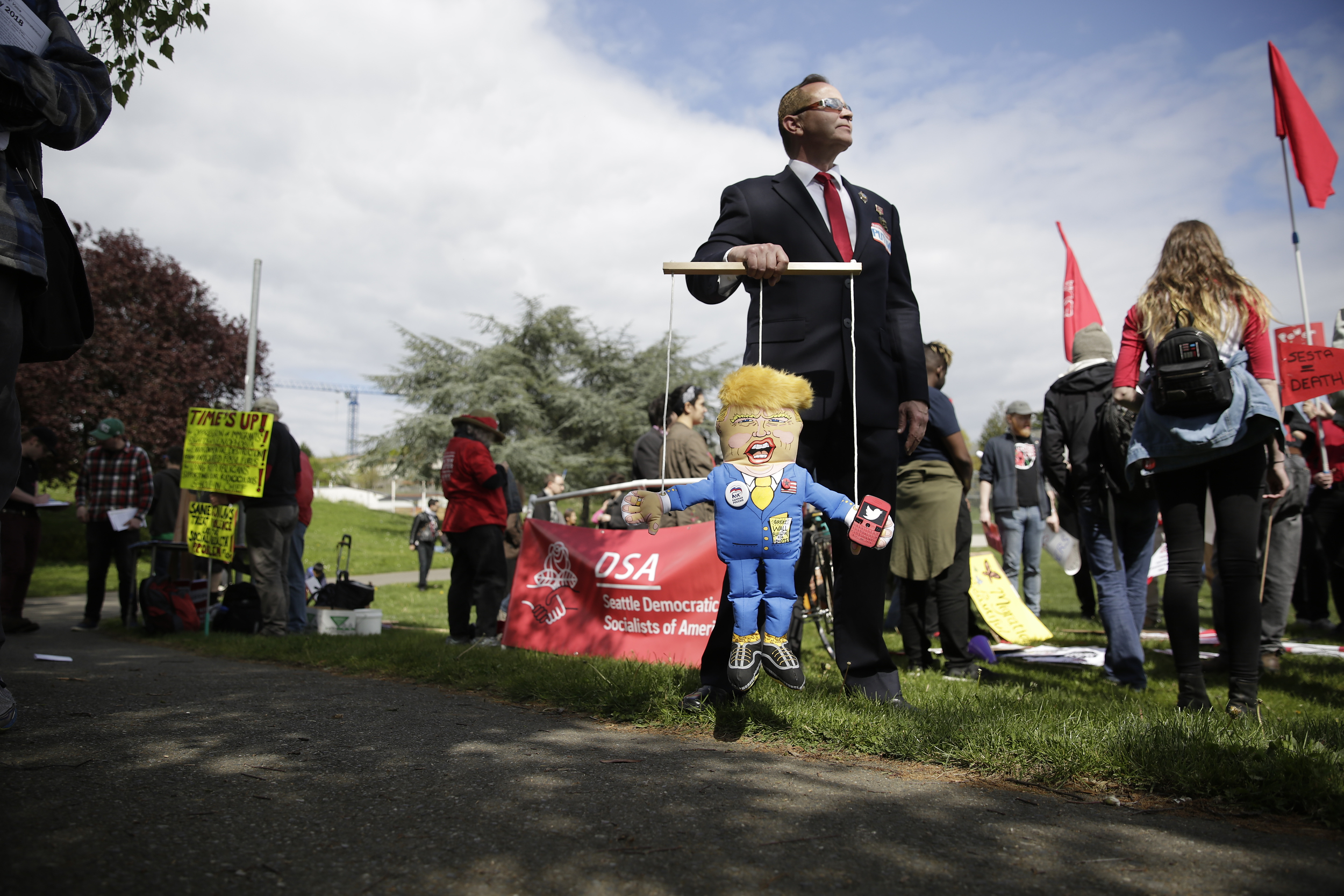 Eric Zorrozua of Bremerton, Wash. dressed as Russian President Vladimir Putin holds a puppet of President Donald Trump during the annual May Day March for Workers and Immigrant Rights in Seattle