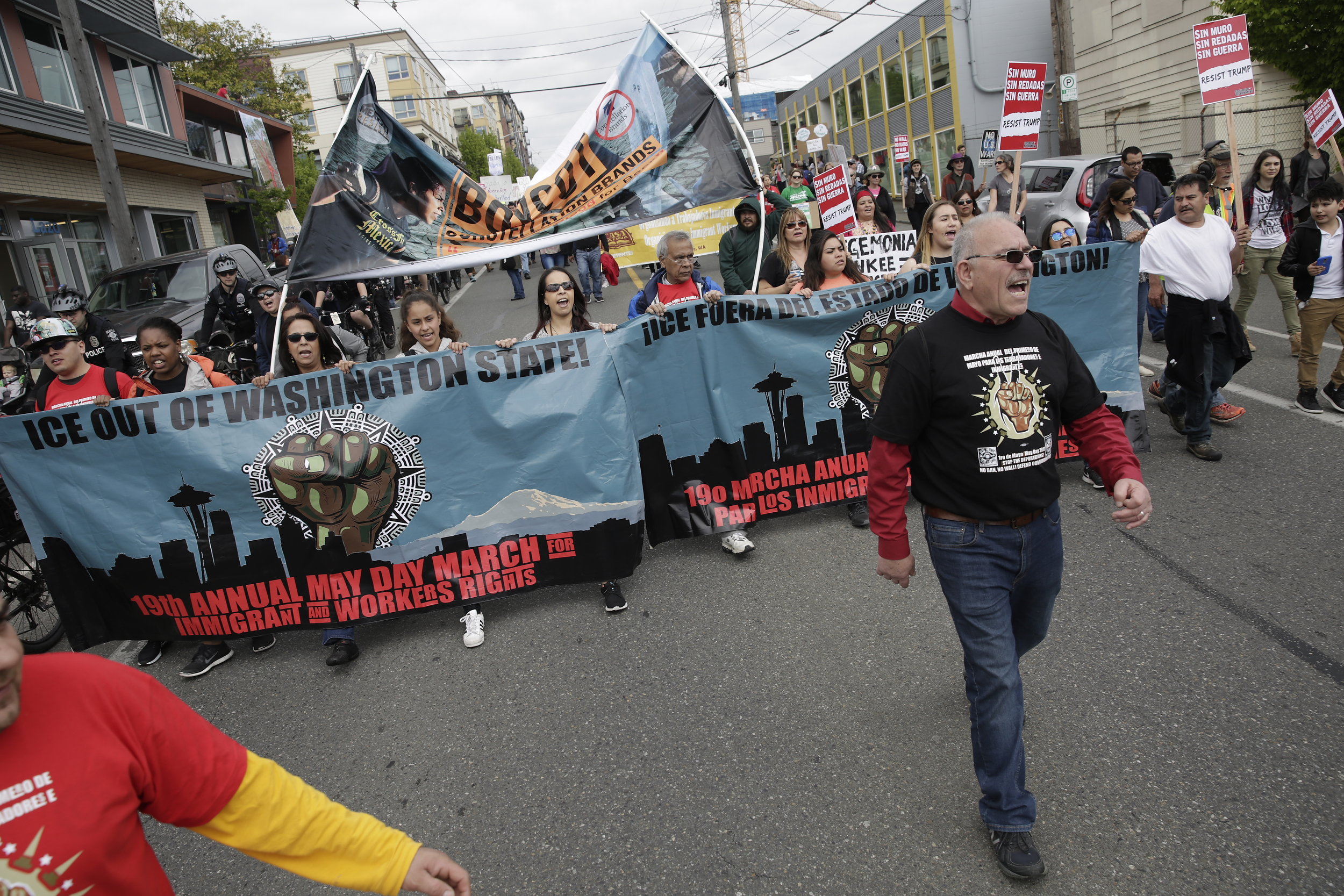 People carry banners as they march down South Jackson Street during the annual May Day March for Workers and Immigrant Rights in Seattle