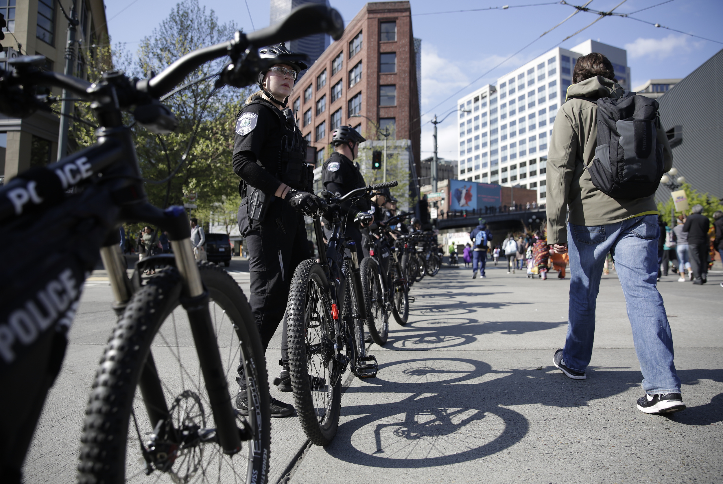 Bicycle officers from multiple departments monitor the annual May Day March for Workers and Immigrant Rights as it progresses along 4th Avenue in Seattle.