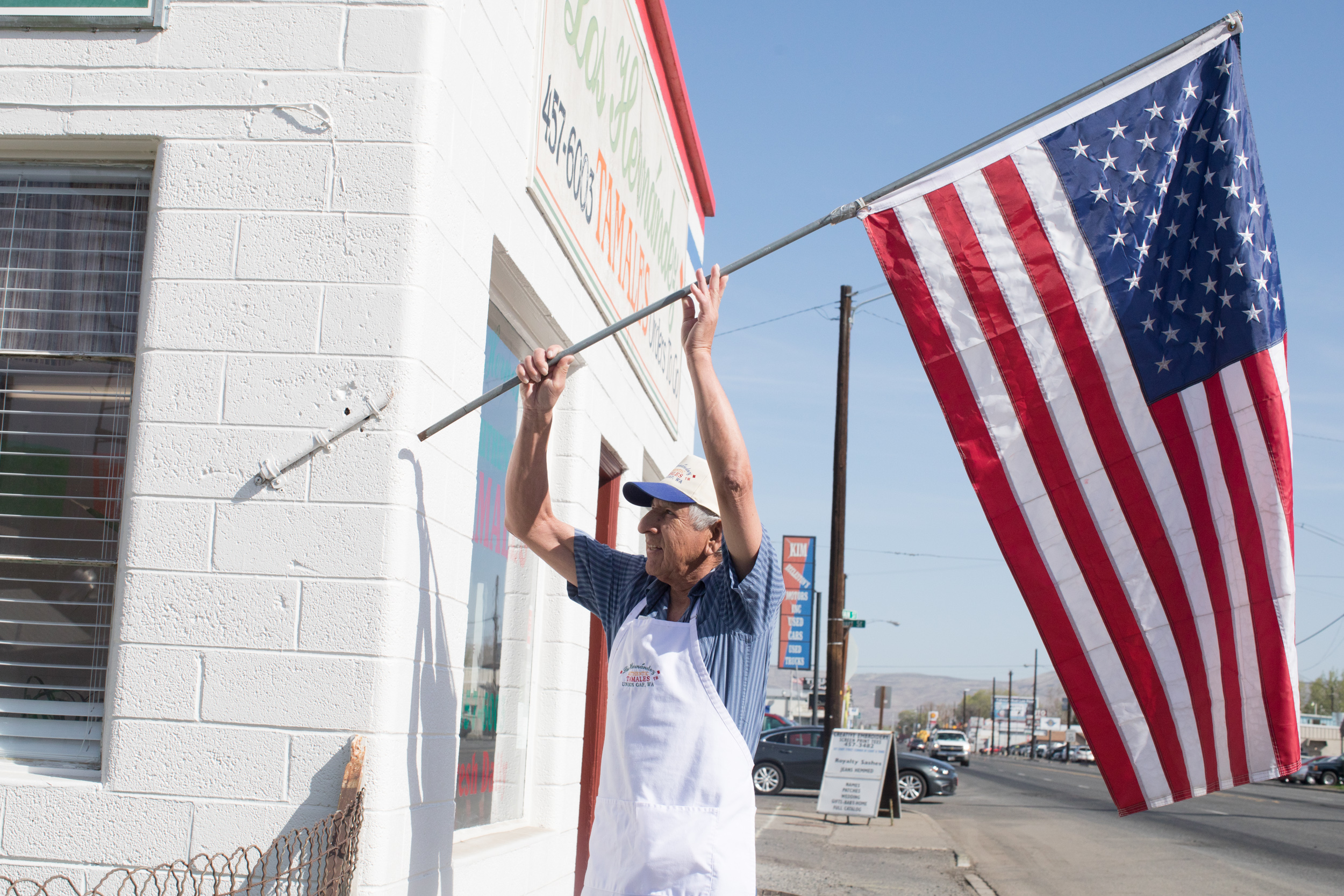 Owner Felipe Hernández hangs an American flag on the exterior of Los Hernández Tamales in Union Gap, Washington, opening the small, award-winning restaurant for yet another day.