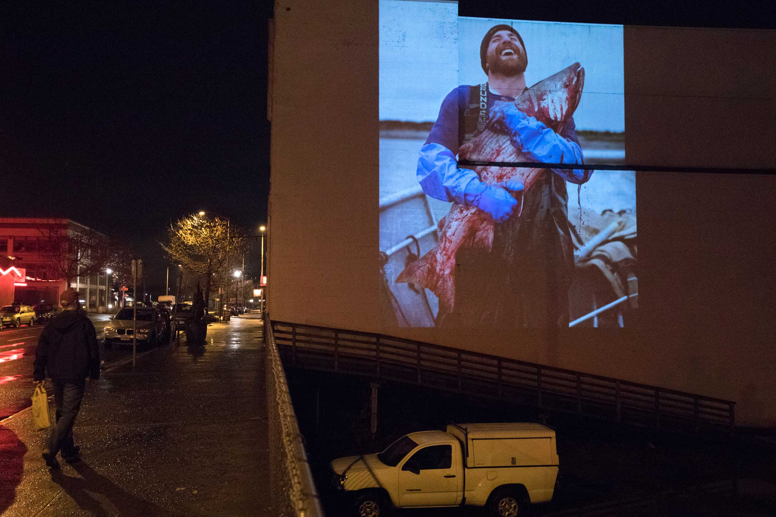 A photograph made by photographer Corey Arnold in Bristol Bay, Alaska, is seen projected on the side of a building along Marine Drive in Astoria.