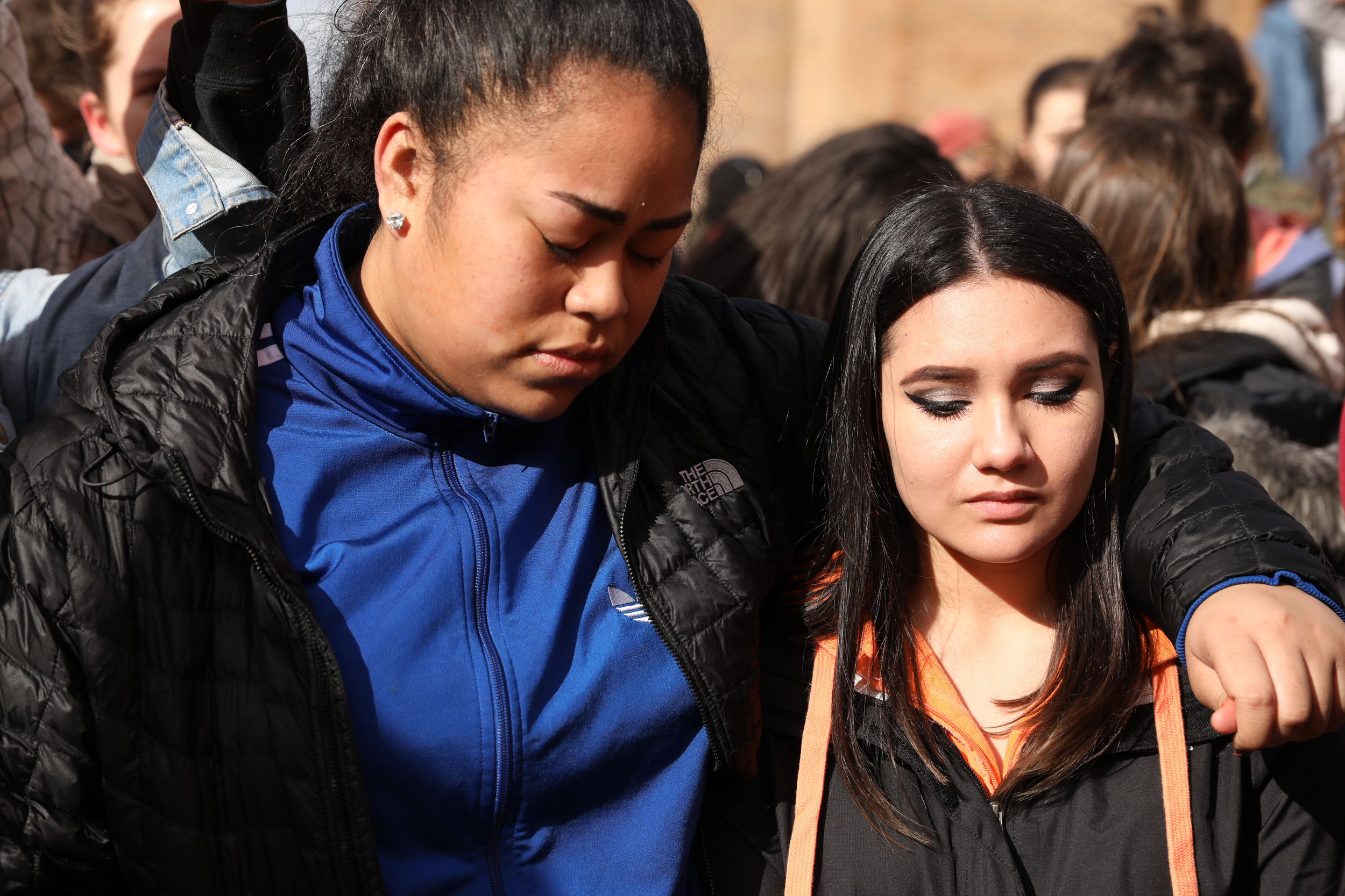 (From left) Nathan Hale High School seniors Precious Anetipa and Melanie Remmers embrace each other during a moment of silence in honor of Parkland High School shooting victims at University of Washington's Red Square, Mar. 14, 2018. (Photo by Matt M. McKnight/Crosscut)