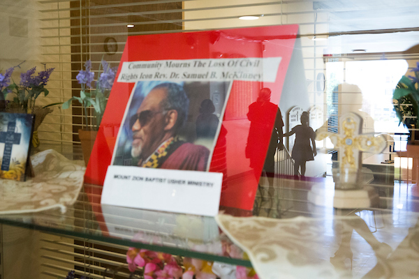 A newspaper clipping of the late Rev. Samuel B. McKinney is pictured in a display case as church members are reflected in the glass following service at Mount Zion Baptist Church in Seattle on Sunday, May 27, 2018.