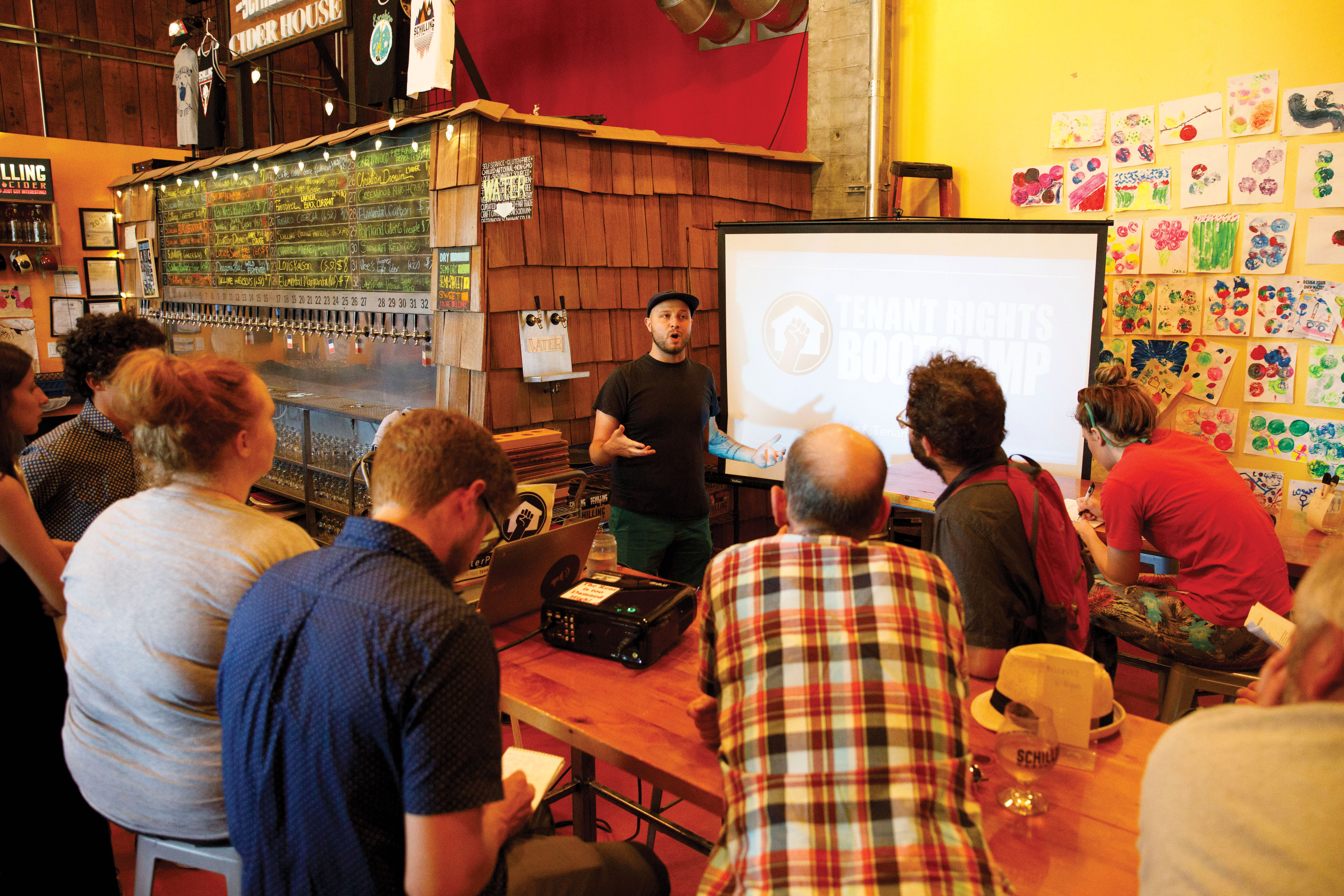 Devin Silvernail, center, leads a Tenant Rights Bootcamp on Wednesday, July 25, 2018 at Schilling Cider House in Fremont, Seattle, WA. The event was hosted by Be:Seattle and provided information on Seattle tenants rights. (Sarah Hoffman/Crosscut)