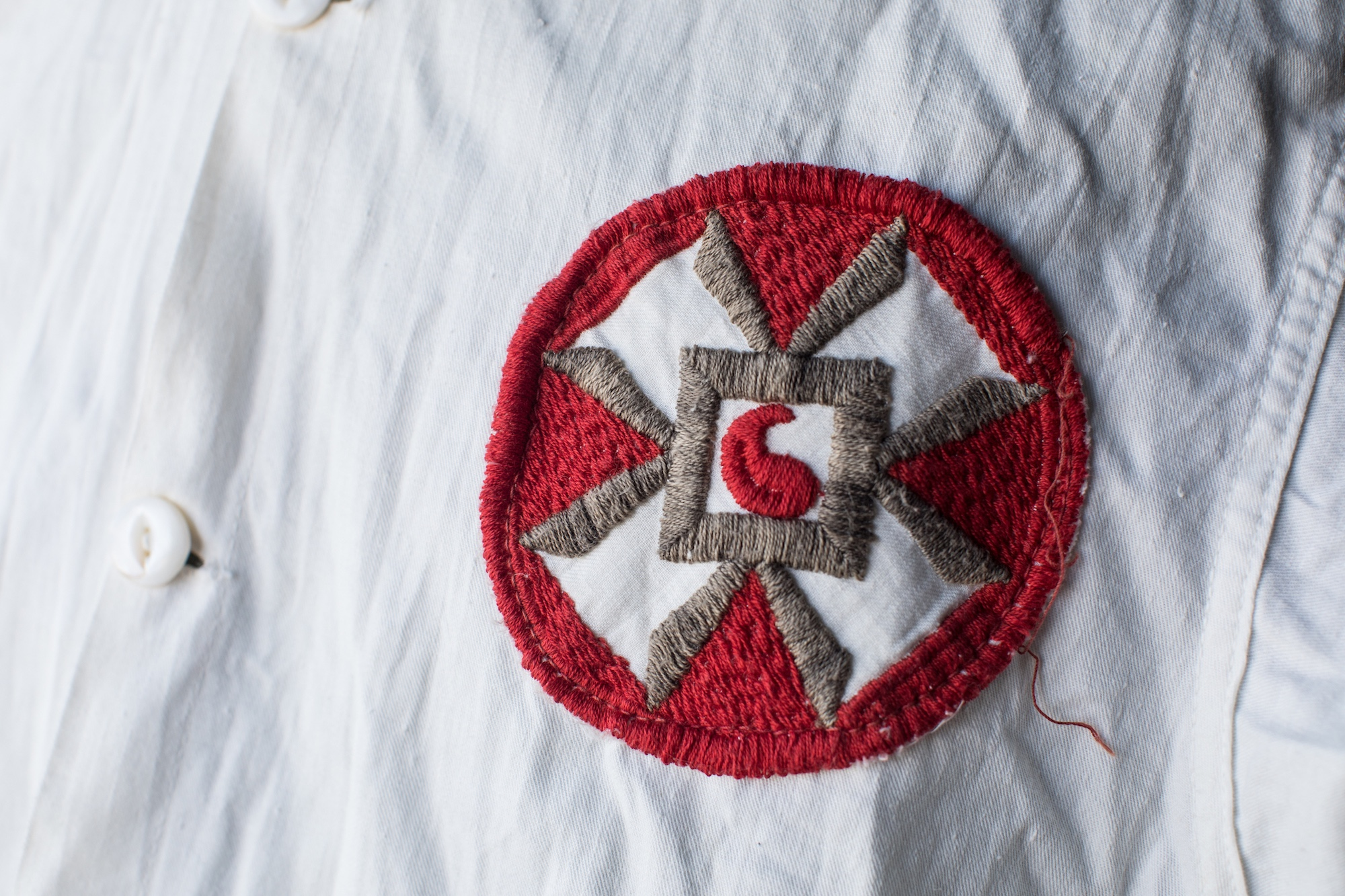 Close-up of a badge sewn into an old Ku Klux Klan robe