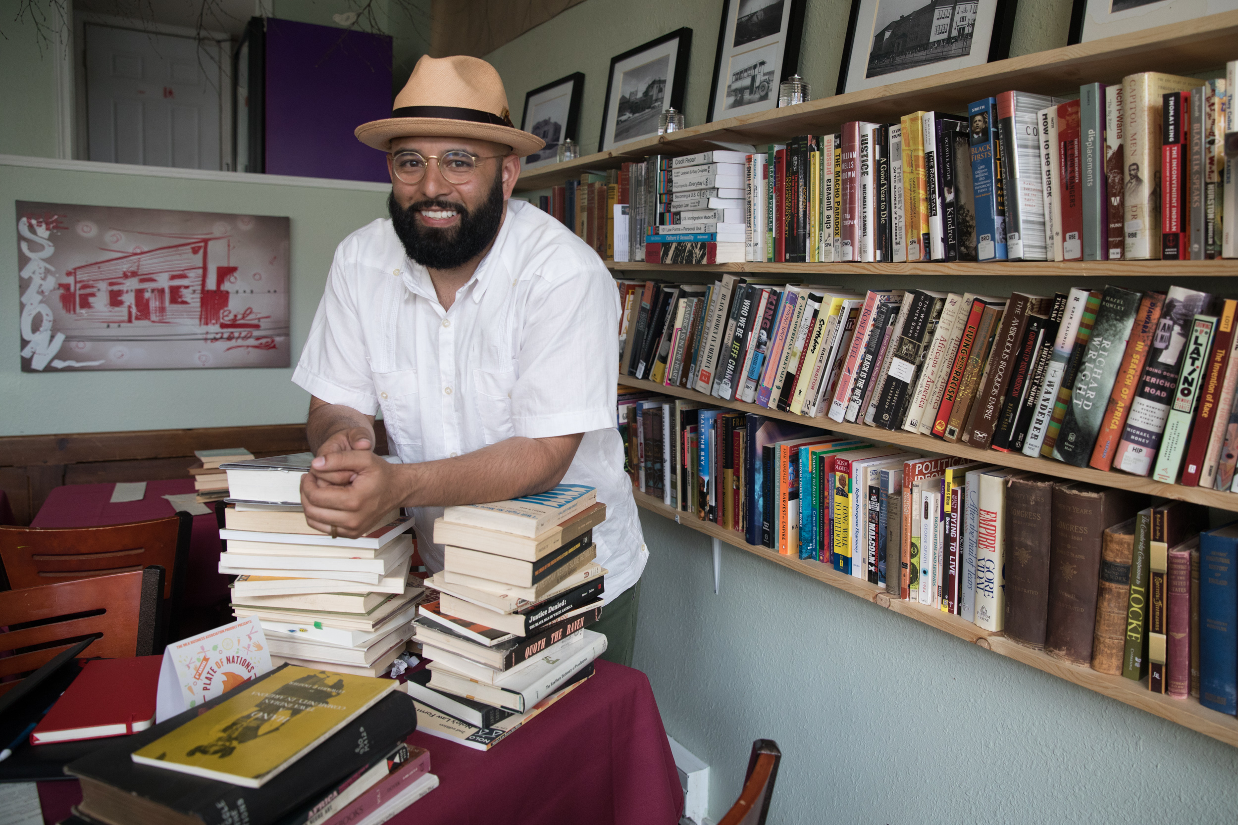 Estelitas Library founder, community organizer and activist Edwin Lindo stands amid an array of books.