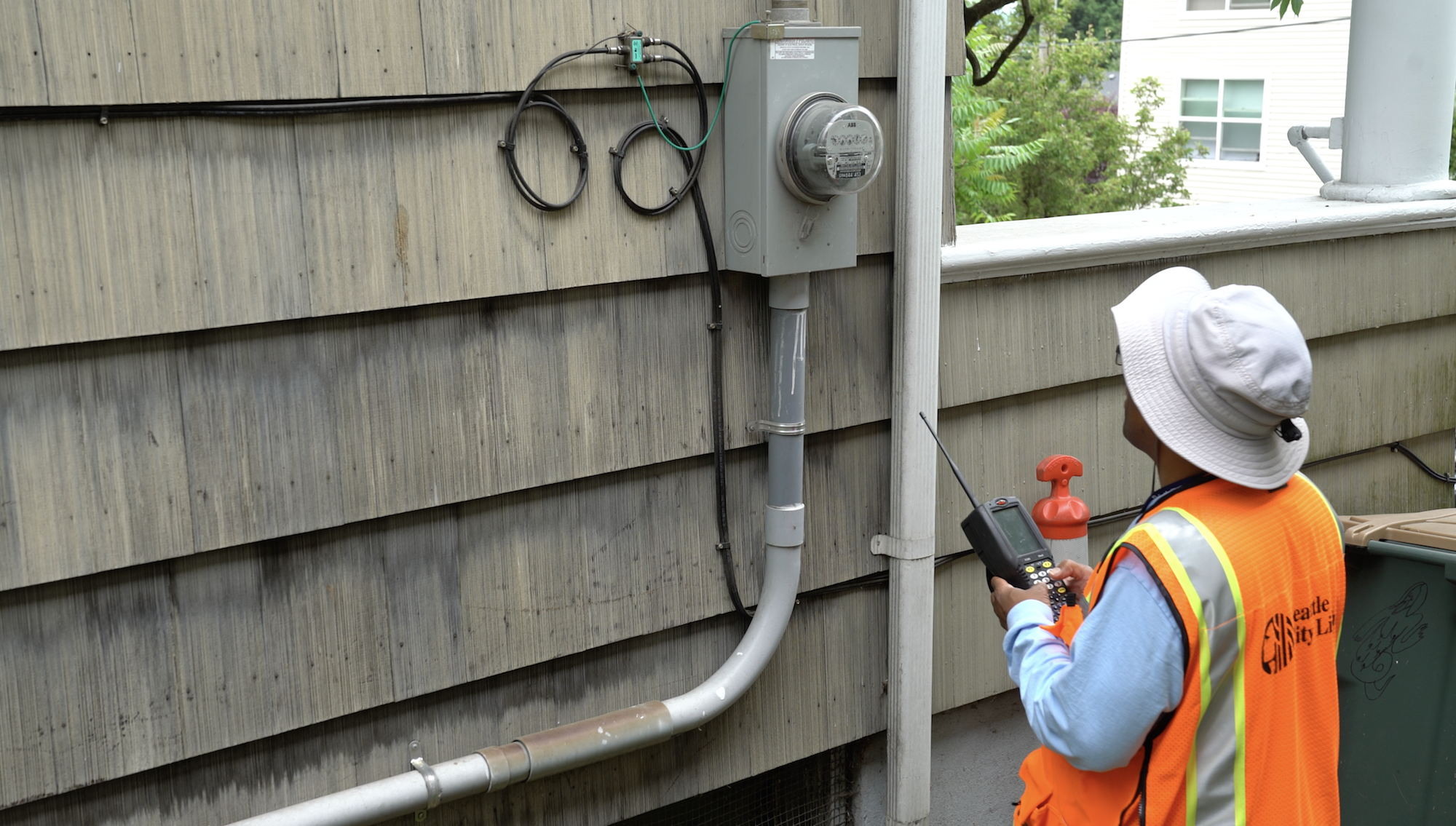 A Seattle City Light employee reads a traditional meter.