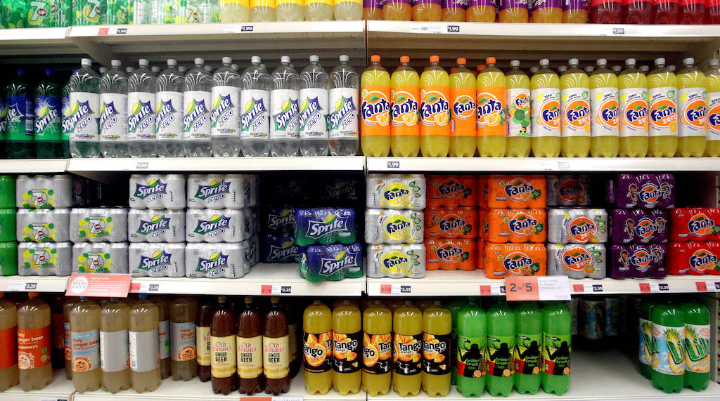 Cans of soda stacked inside a supermarket.