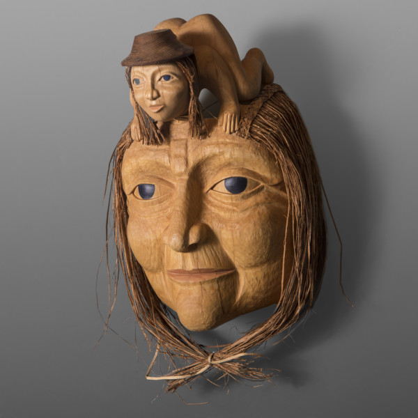 wood carving of a woman's face with a child on forehead