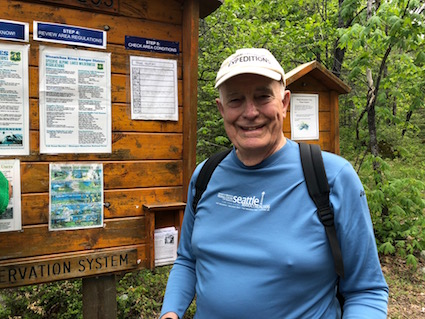 Dan Evans in front of a trailhead information sign