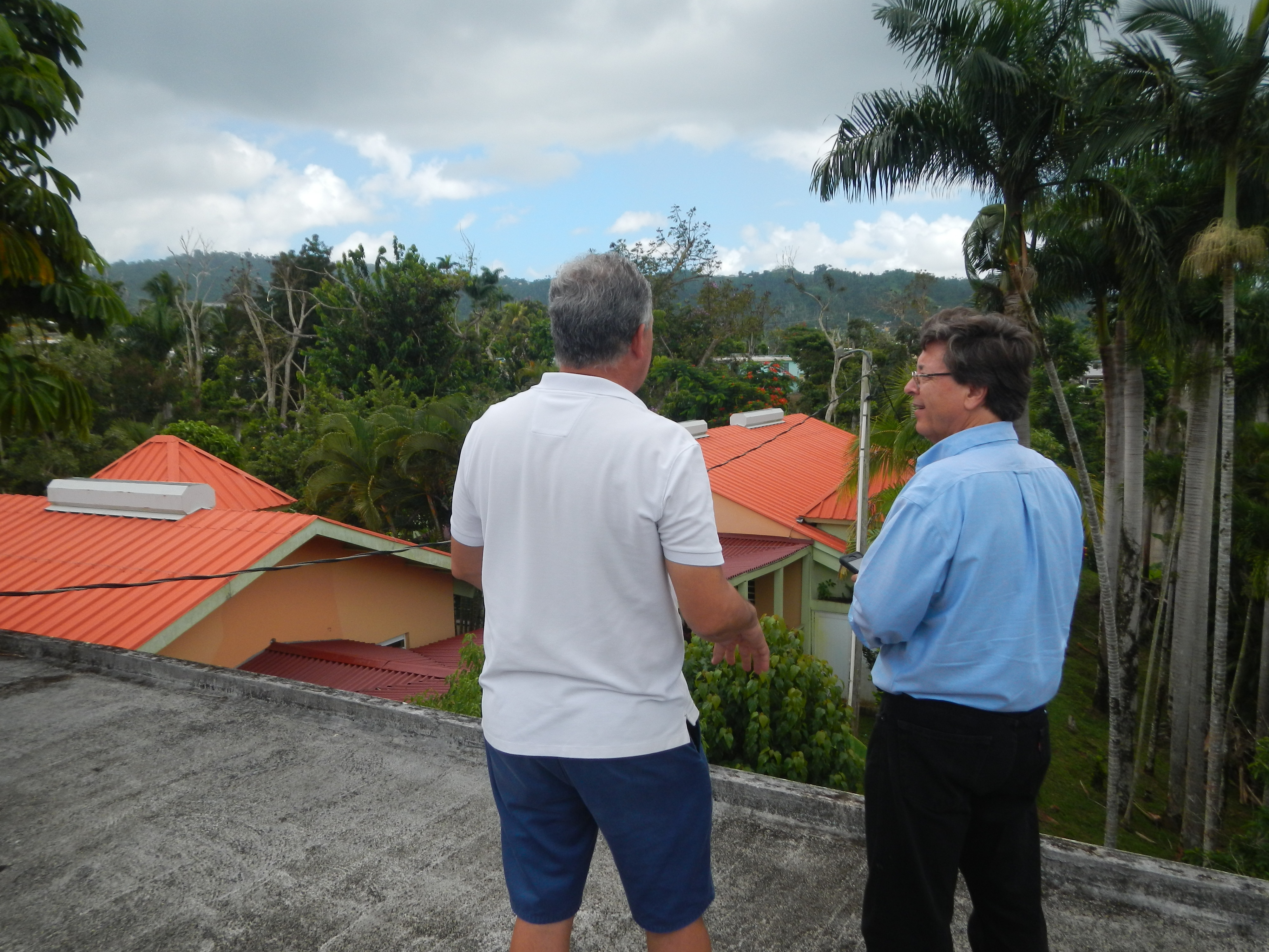 Two people discuss the solar panels on the roof of the school.