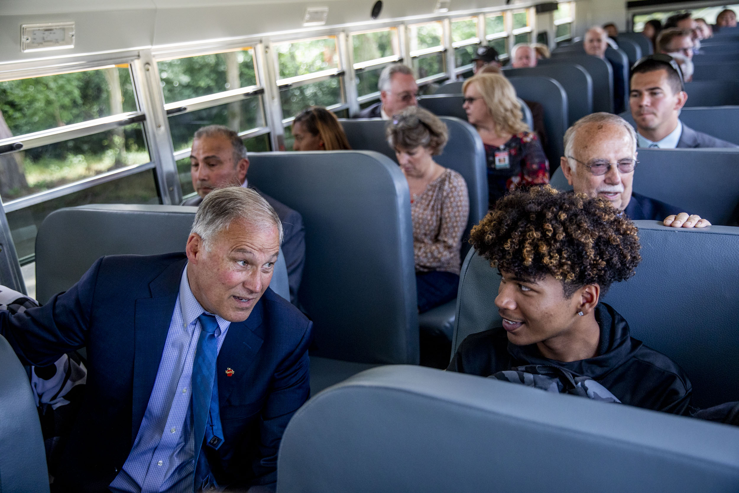 Governor Jay Inslee talks with freshman Malik Goodrum as they ride in the first electric school bus in Washington state during an event at Franklin Pierce High School in Tacoma on June 17, 2019. (Photo by Dorothy Edwards/Crosscut)