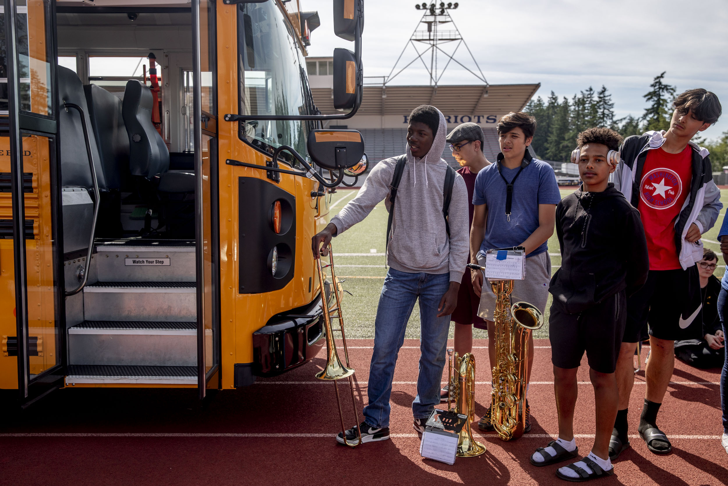 Students listen to speakers next to the first electric school bus in Washington state during an event with Governor Jay Inslee at Franklin Pierce High School in Tacoma on June 17, 2019. (Photo by Dorothy Edwards/Crosscut)