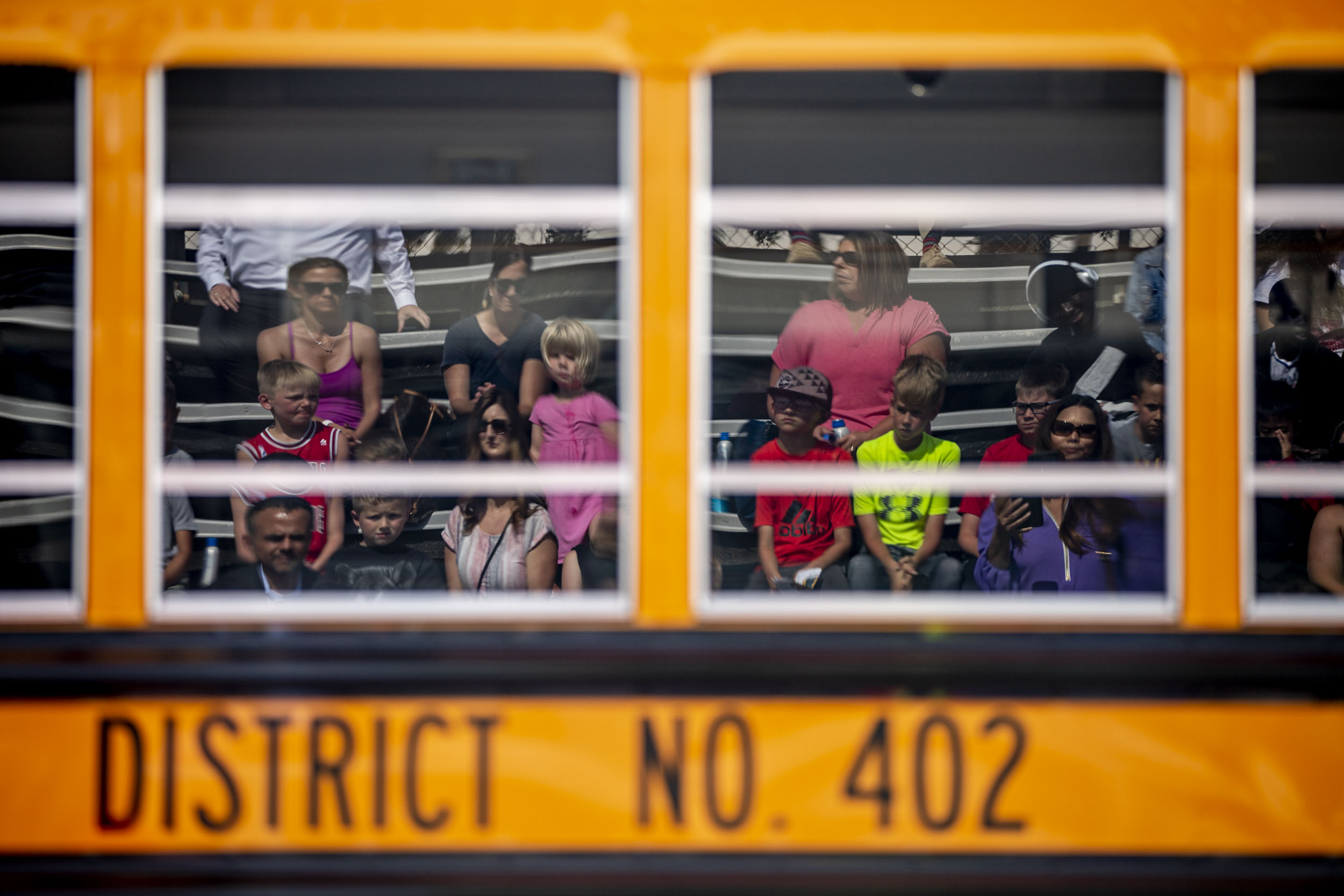 Attendees listen to speakers in front of the first electric school bus in Washington state during an event with Governor Jay Inslee at Franklin Pierce High School in Tacoma on June 17, 2019. (Photo by Dorothy Edwards/Crosscut)
