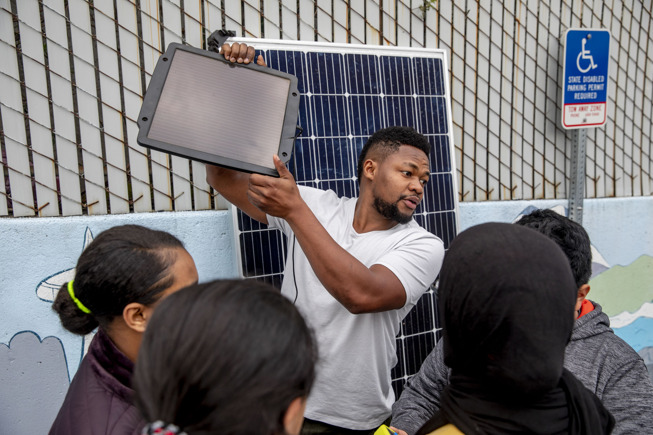 "Edwin Wanji, center, teaches a group of kids from the Lake City Young Leaders program about how to work a solar panel at the Lake City Community Center on April 1. Wanji is the owner and founder of Sphere Solar Energy in Seattle and is often invited to talk to students about opportunities in solar. ""I'm trying to create excitement around this field. It's renewable energy, it's exciting, there will always be more sunlight tomorrow,"" he says. ""It's encouraging to see the kids' excitement about it."" (Photo by Dorothy Edwards/Crosscut)"