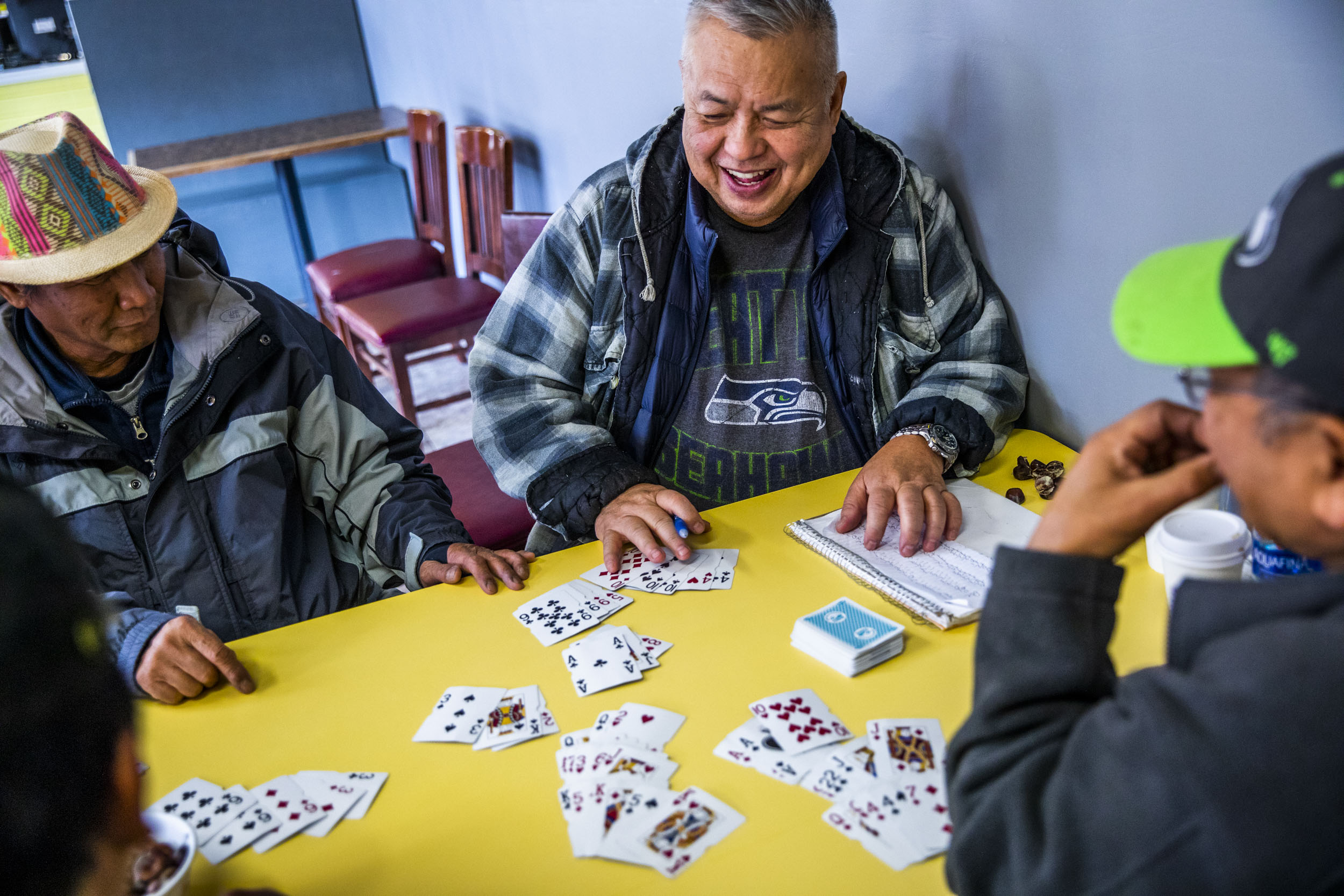 Ed Campos, 68, of Seattle plays a game of cards with other regulars at King Donuts in Rainier Beach on Wednesday, Nov. 14, 2018. Campos says he has been coming to King Donuts for the last 30 years.