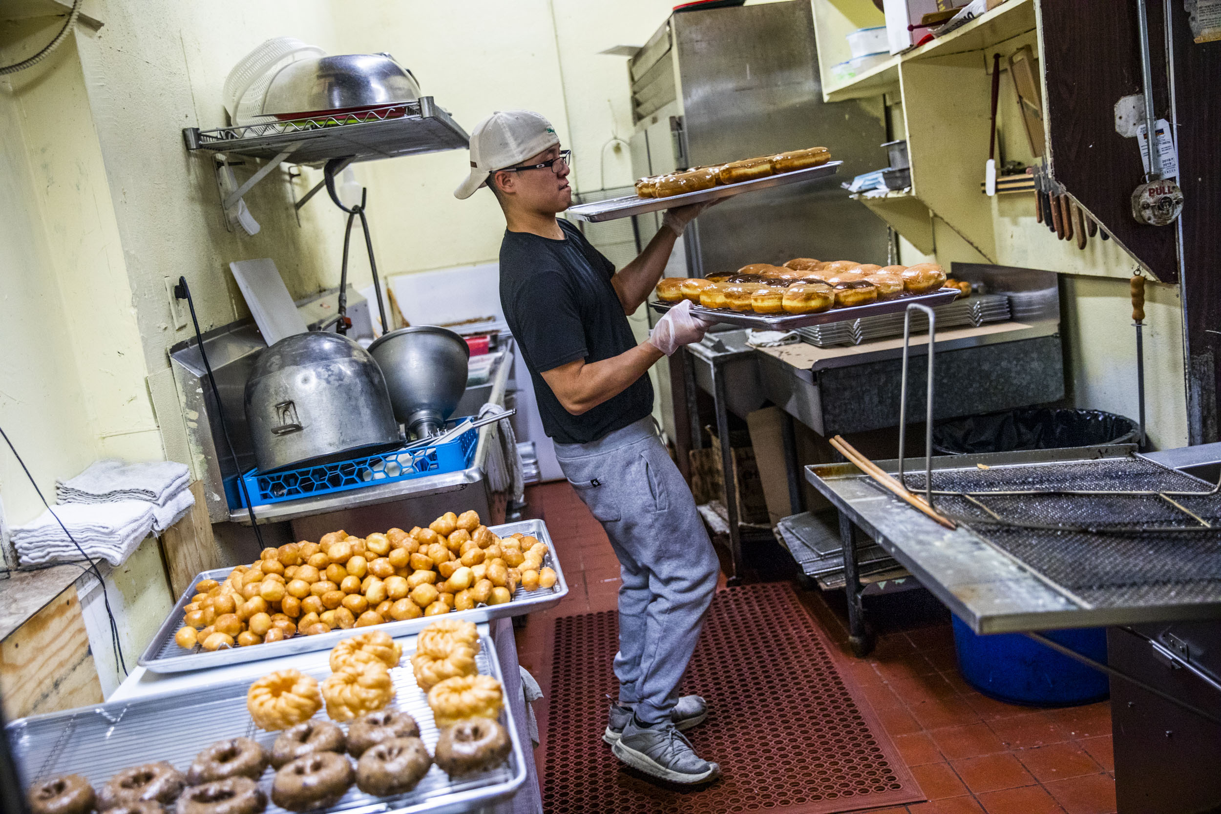 Travis Chhuor, 30, prepares doughnuts in the morning at King Donuts in Rainier Beach on Sunday, Nov. 18, 2018. Chhuor is the sole baker for the shop and often gets to work at 3 a.m.to start on the day's doughnuts.