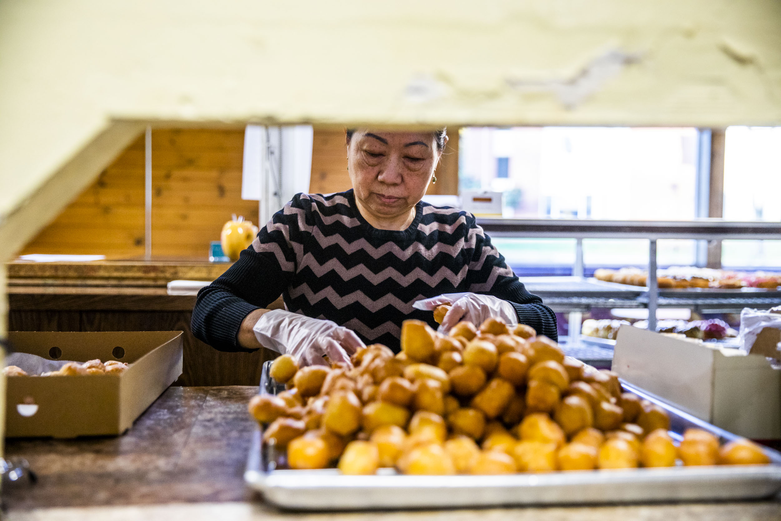 Owner Kim Sok fills a box with doughnuts at King Donuts in Rainier Beach on Sunday, Nov. 18, 2018.