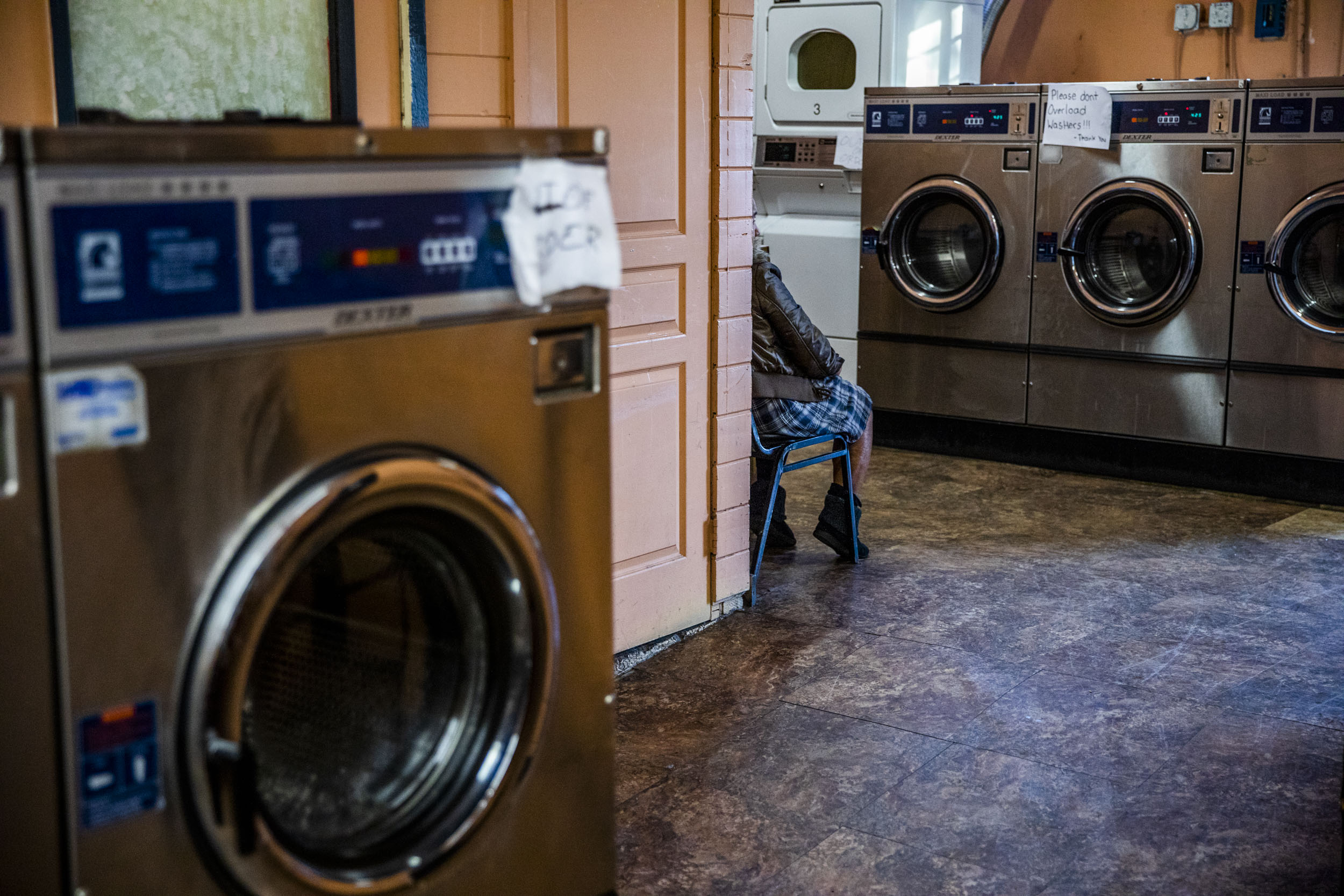 A woman waits for her laundry to finish at King Donuts in Rainier Beach on Sunday, Nov. 18, 2018.