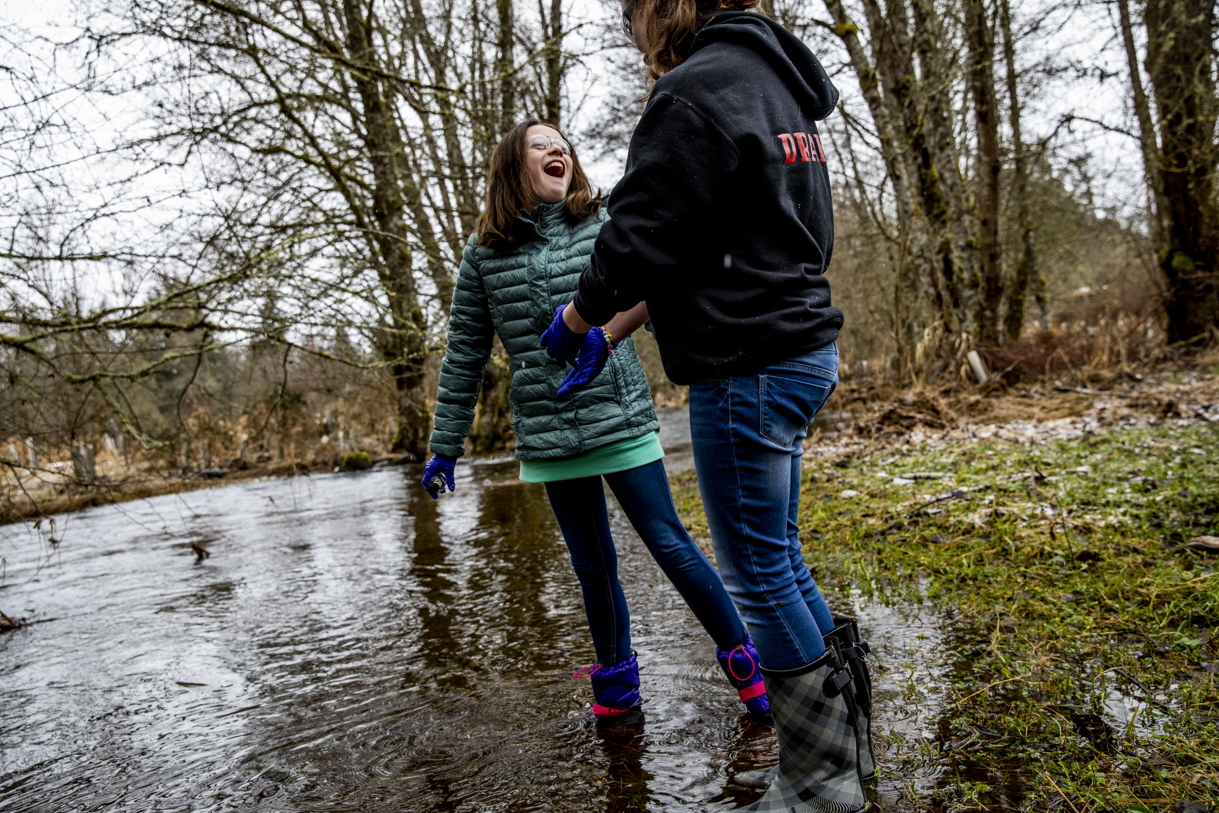 Sixth graders Taylor Drake, right, and Lexi Thompson collect water samples from Muck Creek.