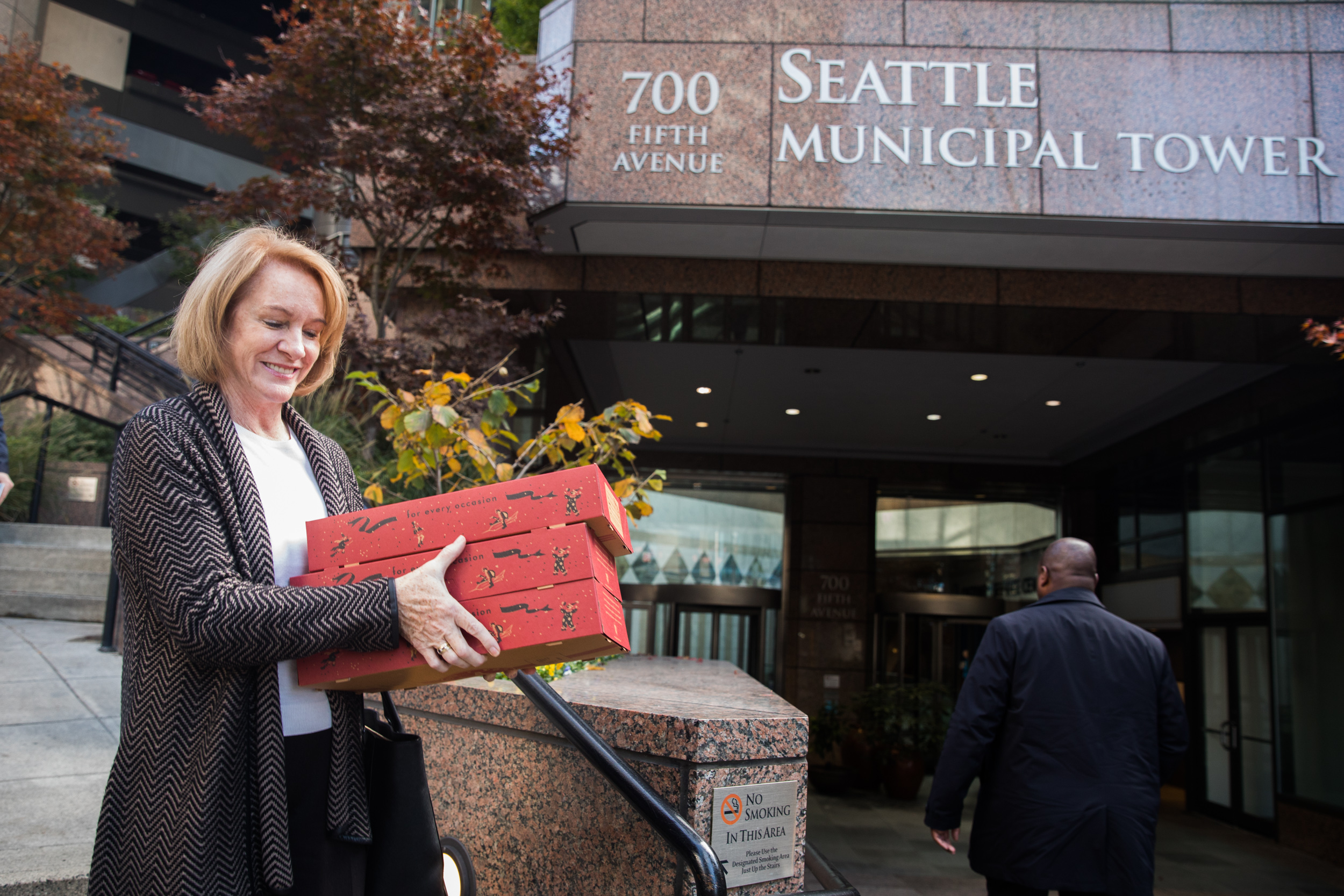 Outside the Seattle Municipal Tower, Mayor Jenny Durkan carries donuts for her staff, Nov. 8, 2018. (Photo by Matt M. McKnight/Crosscut)