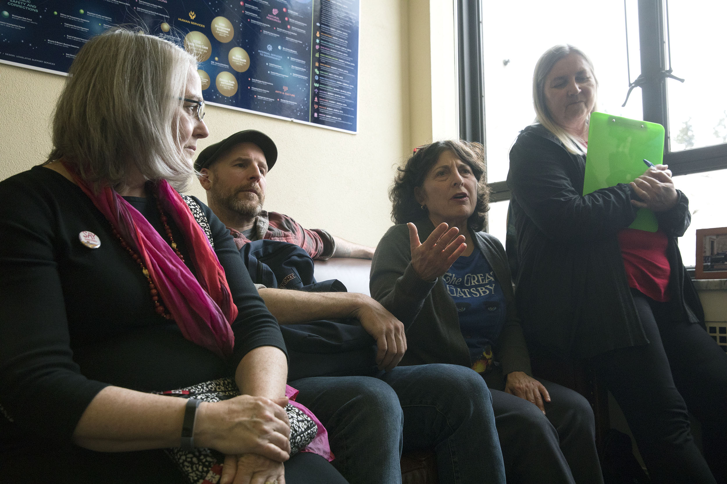 Lee Micklin of Cleveland STEM High School (center right) sits with other librarians and talks with Washington state Sen. Reuven Carlyle during a group lobbying effort at his Olympia office, April 2, 2019. (Photo by Matt M. McKnight/Crosscut)