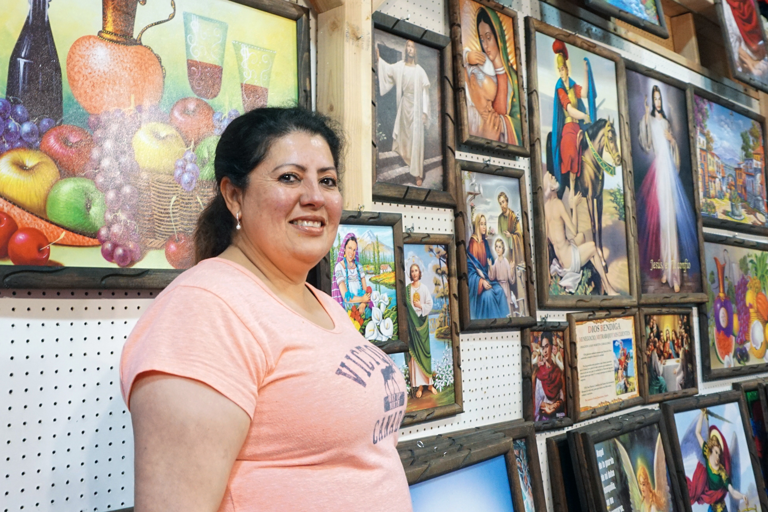 Lopez poses with her framed art work she sells.