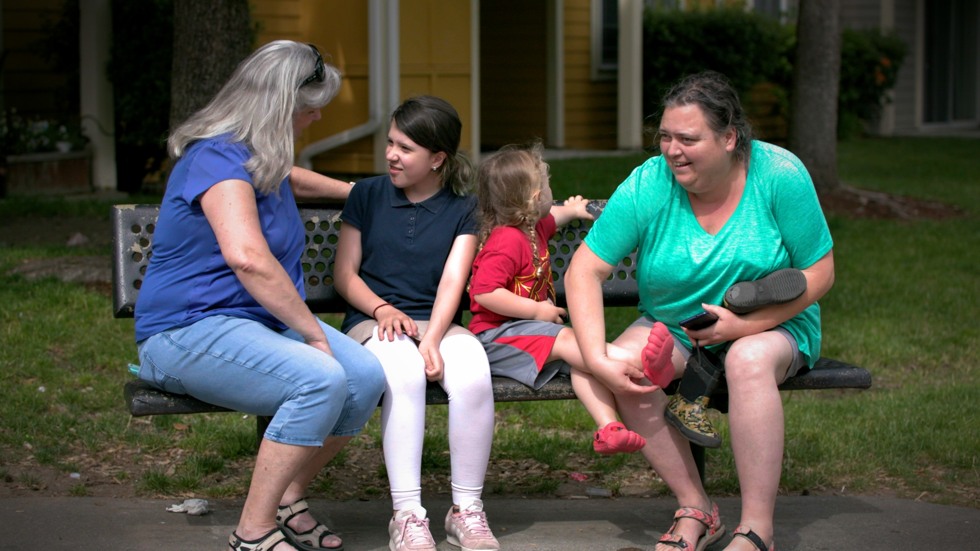 A grey haired woman, Julie Brenaman, sits on a bench talking with two children and their grandmother, who's trying to put a shoe on the smaller child.