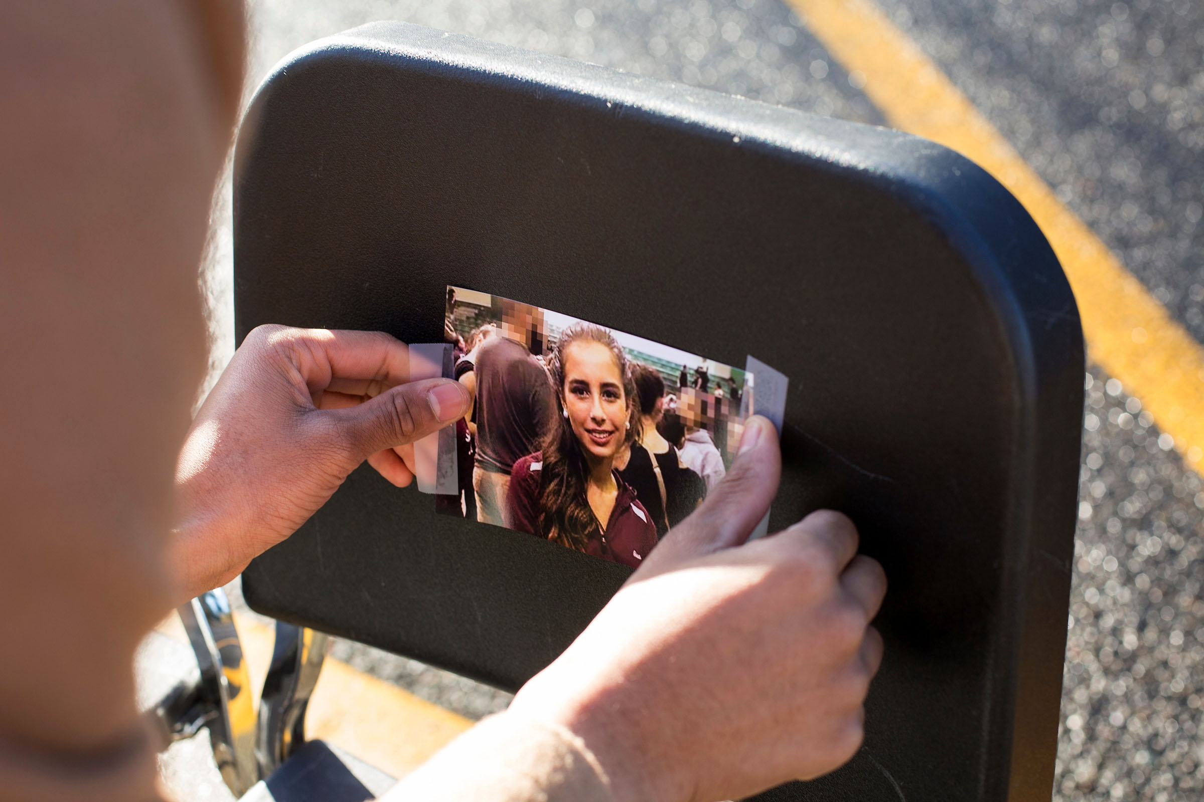 A Tumwater High School student tapes a photo of a victim of the high school shooting in Parkland, Florida in February. (Photo by David Ryder for Crosscut)