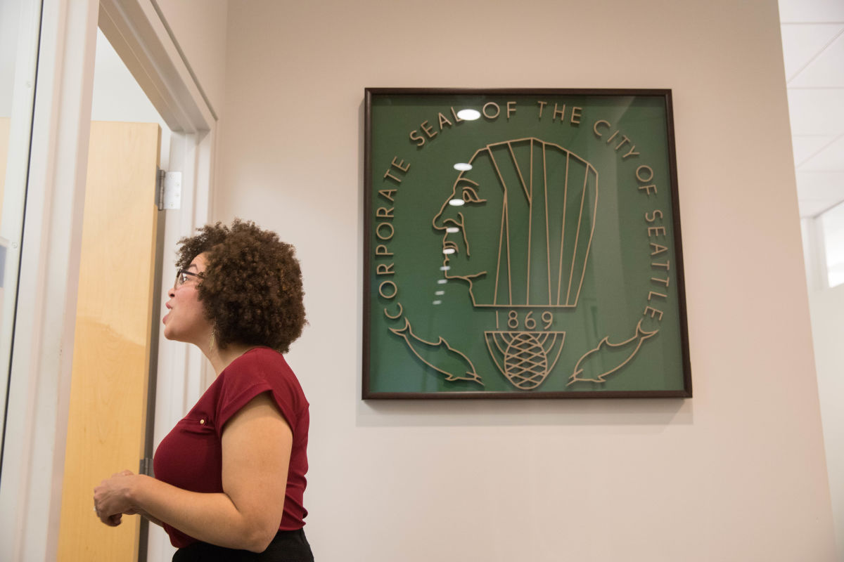 Harris-Talley talks to a central staff team member behind-the-scenes at City Hall, standing in front of the city's original seal.