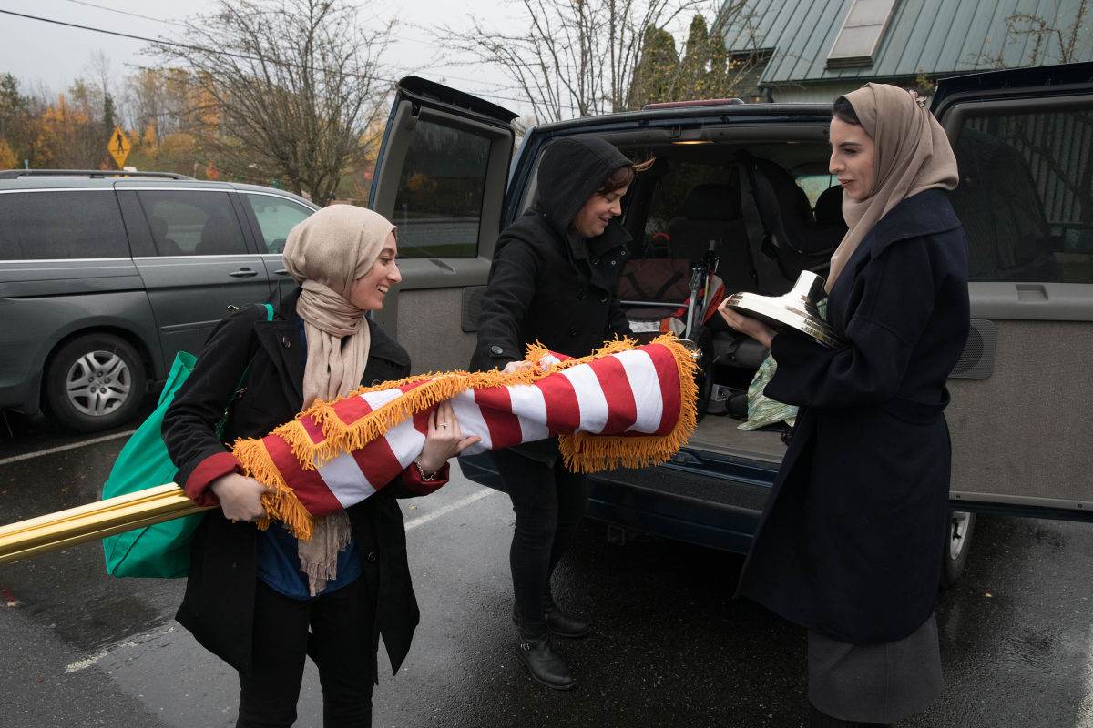 Council on American Islamic Relations team members (from left) Varisha Khan, Sarah Stuteville, and Izdihar Bailey unload American flags from their car to be placed inside St. Paul's Episcopal Church during a Faith Over Fear Roadshow visit to Mt. Vernon.
