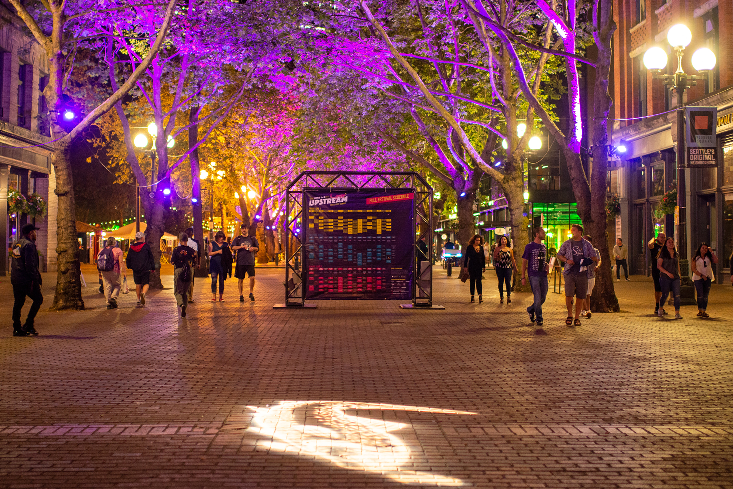 Upstream Music Festival attendees walk from one showcase to another along Occidental Avenue South near midnight on Saturday, June 2nd, 2018, during the festival's second year.