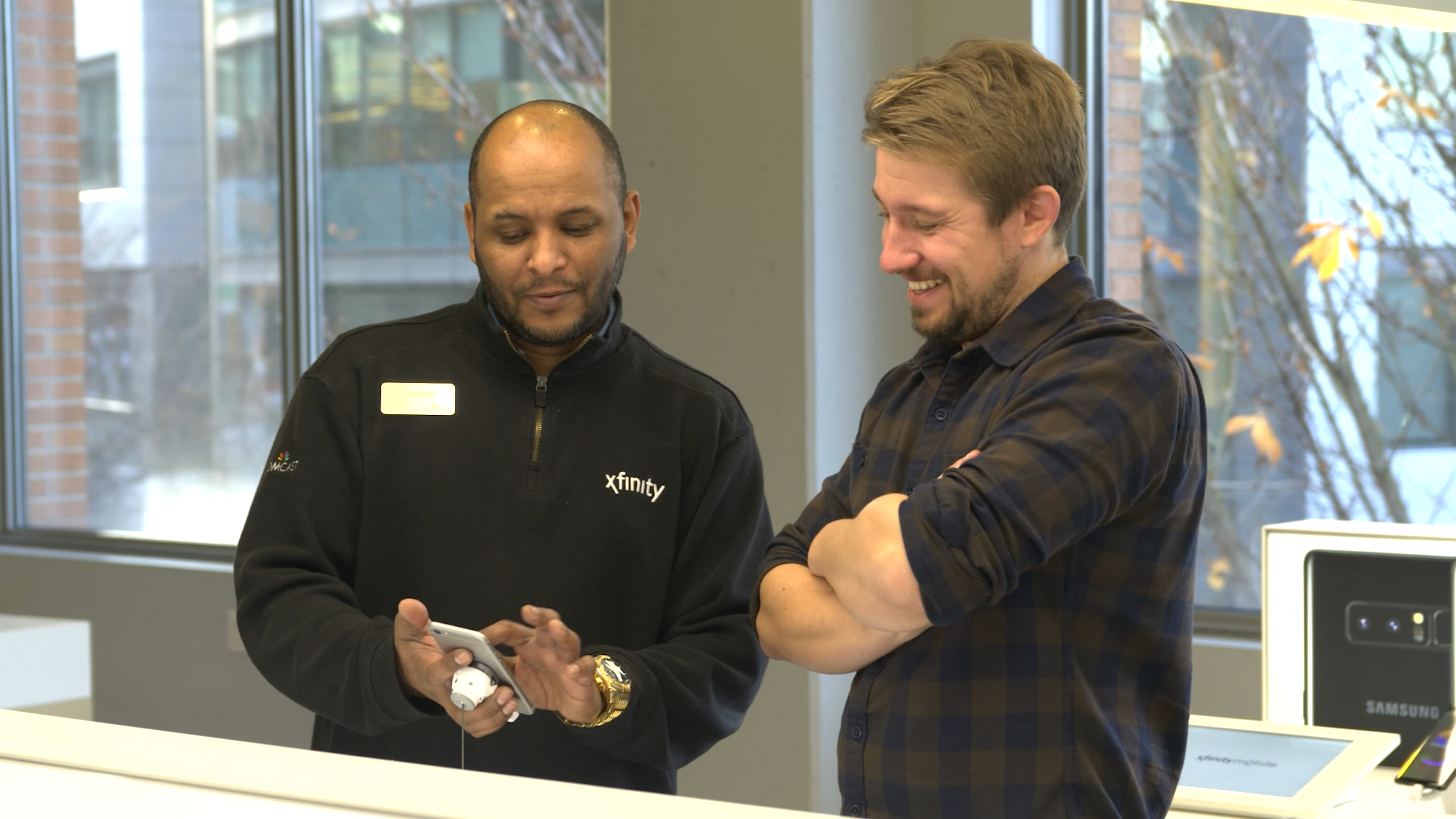 An Xfinity employee shows a customer the features of a new cell phone.