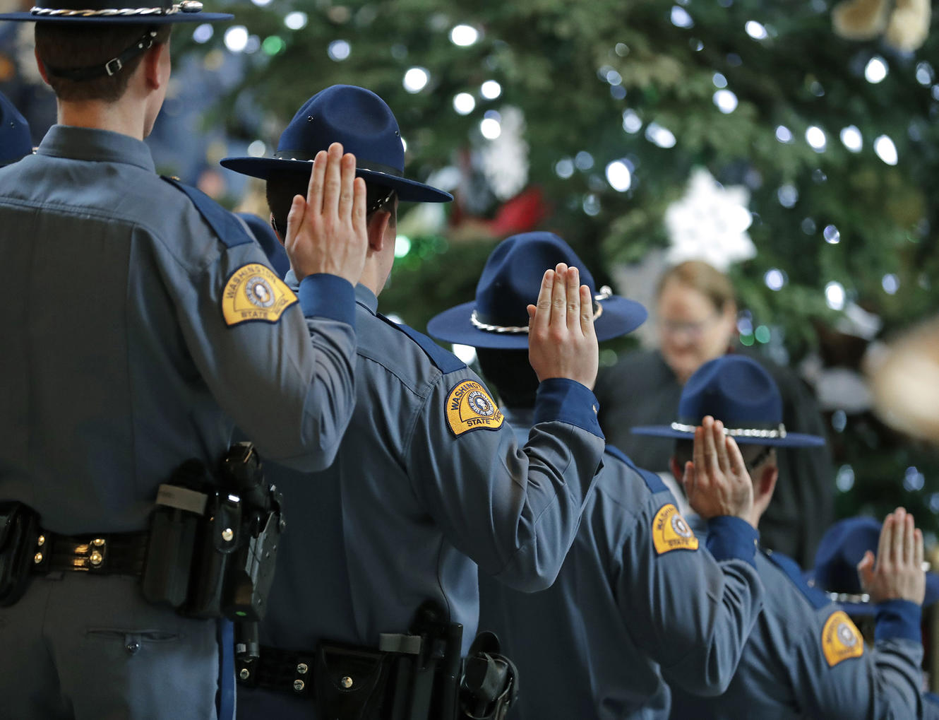 New Washington State Patrol troopers taking part in a graduation ceremony raise their right hands and take the Oath of Office, Thursday, Dec. 13, 2018, in the Rotunda at the Capitol in Olympia, Wash. The class of 31 troopers completed more than 1,000 hours of training and will now work for the WSP across the state. (AP Photo/Ted S. Warren)