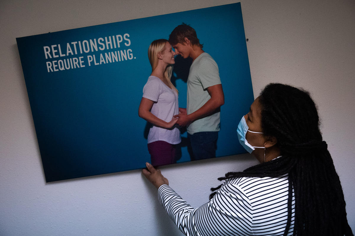 Sharon Dudash removes a poster that has two people on it holding hands, touching noses
