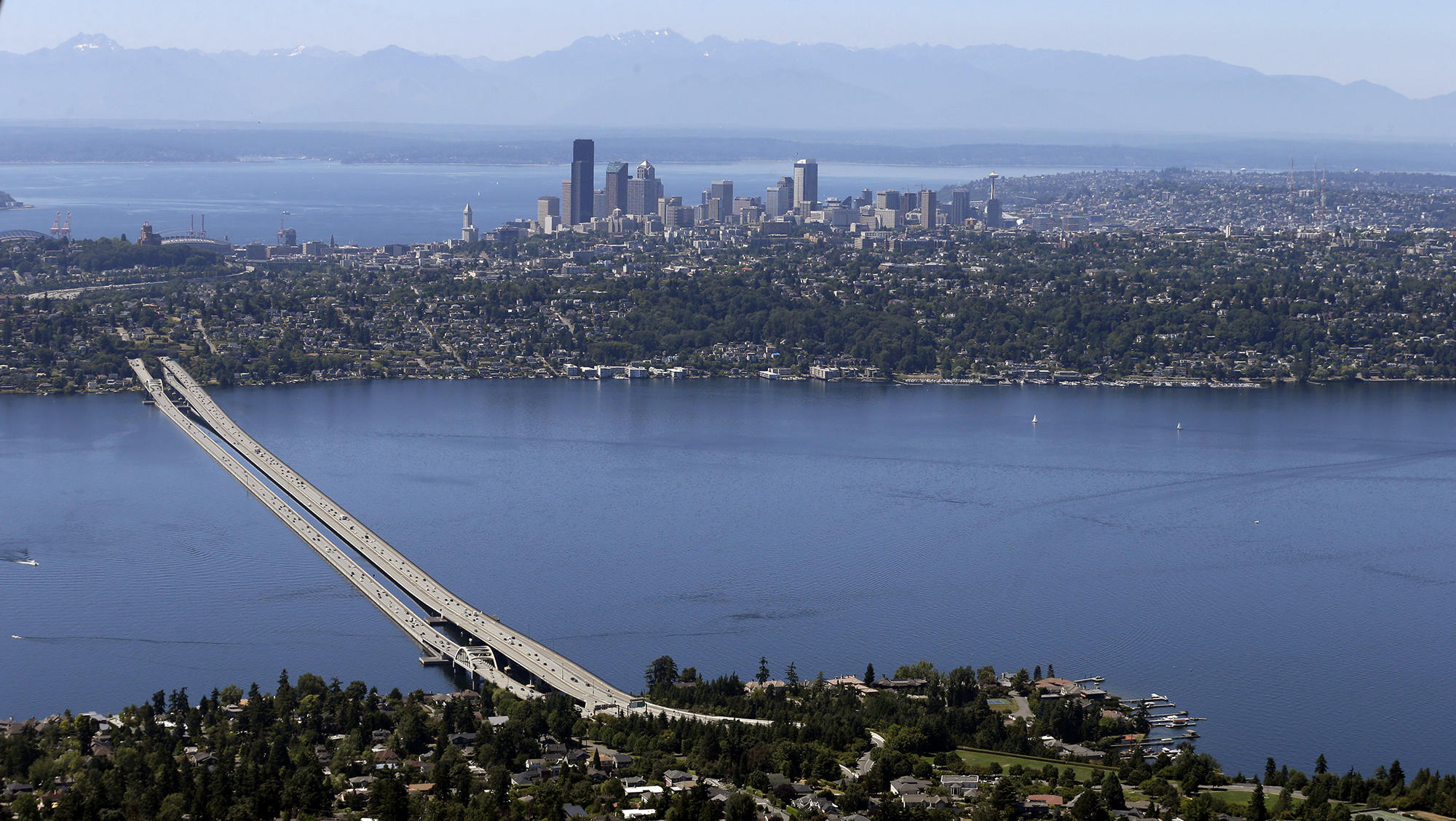Seen from above, a hazy blue mountain range stands in the distance, with a city skyline and surrounding suburbs between two bodies of water. A floating highway bridge leads across the water.