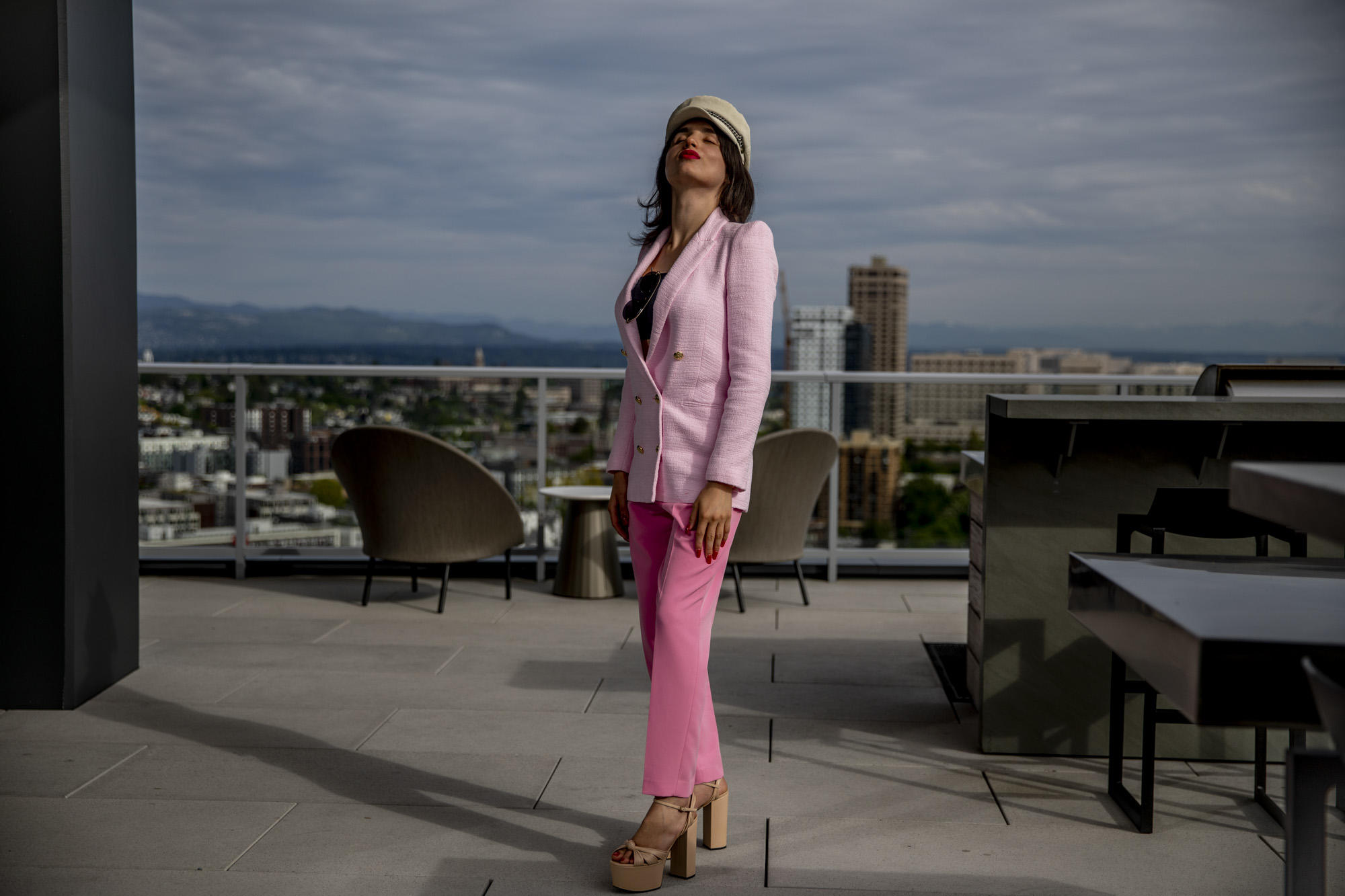 On a concrete rooftop patio wit ha city skyline nad mountains in the background, a person in a pink suit stands and looks up at the sky.