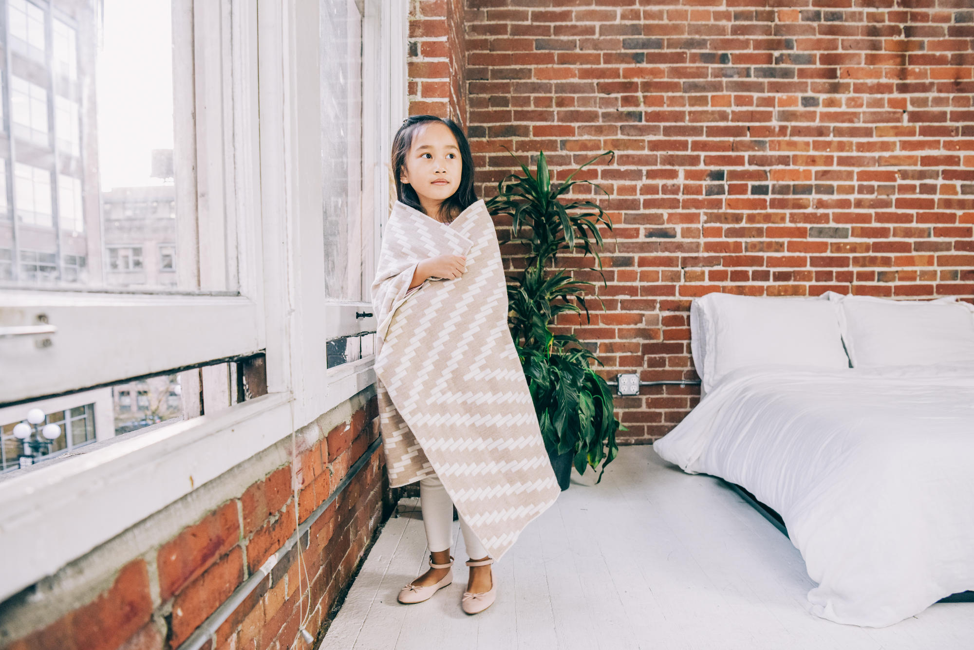 kid by window wrapped in blanket