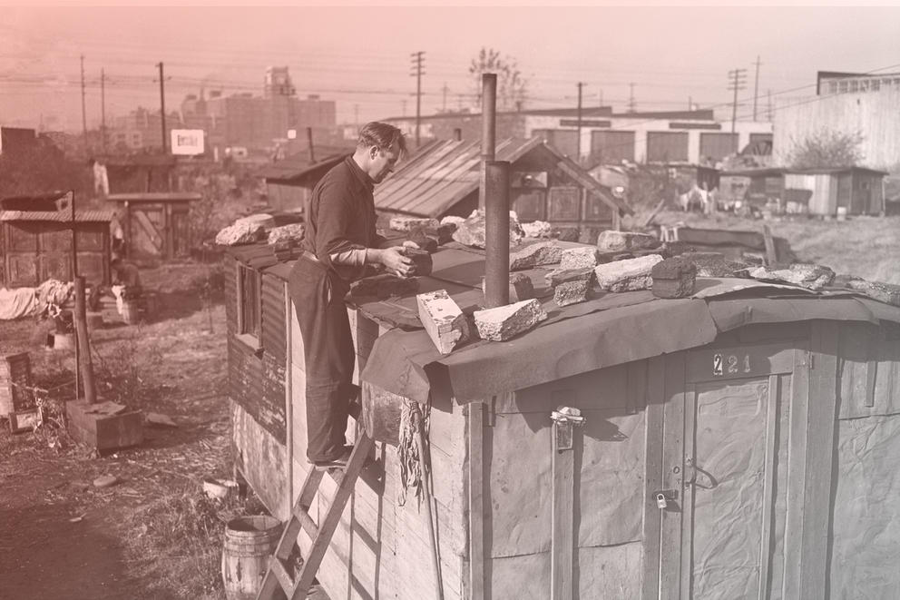 Edwin Hill repairing roof of shack in Hooverville, Seattle, November 1939, with tarpaper weighted down with chunks of cement. Katie Wilson writes that one can view today's economic crisis as loosely analogous to the Great Depression of the 1930s, but with a crucial difference: This time capitalism has nowhere left to go, writes Katie Wilson. (Seattle Post-Intelligencer via MOHAI)