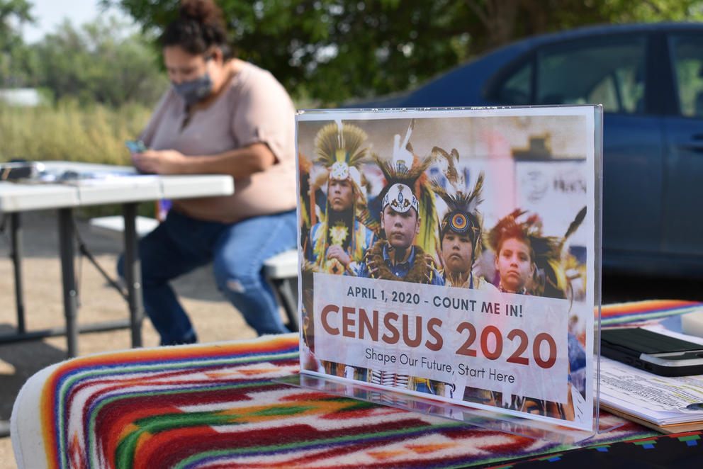 """A person in a mask sits at a table next to a car. In the foreground on a blanket-covered table, a plastic sign reads: Census 2020. Shape our future, start here"""""""