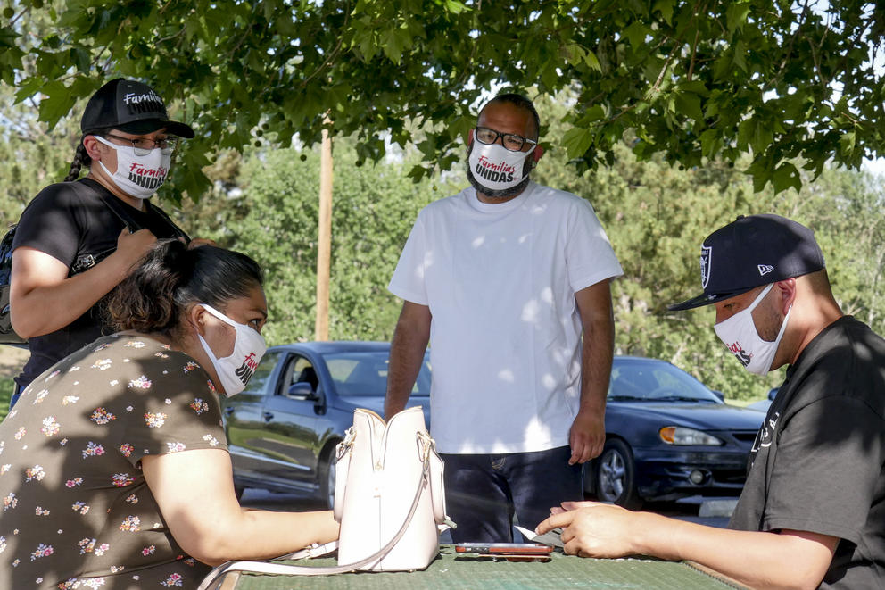 People with masks around an outside table