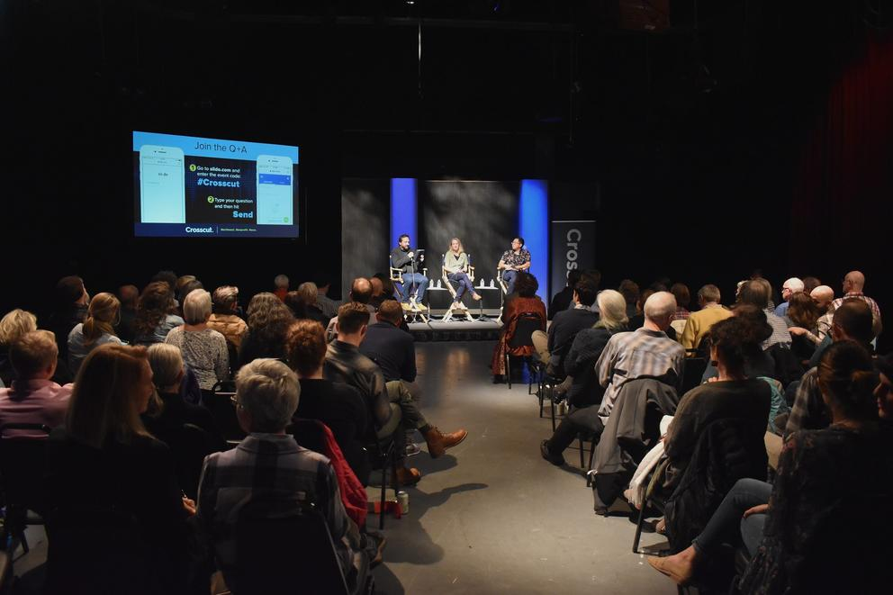 Three panelists discuss climate change before an audience in a darkened studio