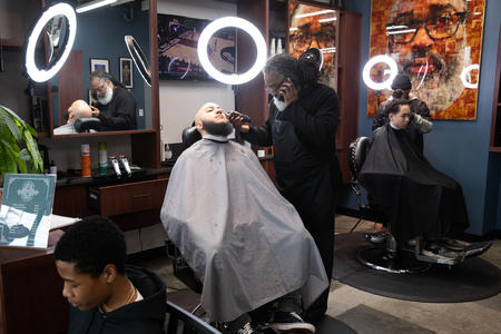 A man gets his beard trimmed by a barber in a barbershop, selfie lights surround him.